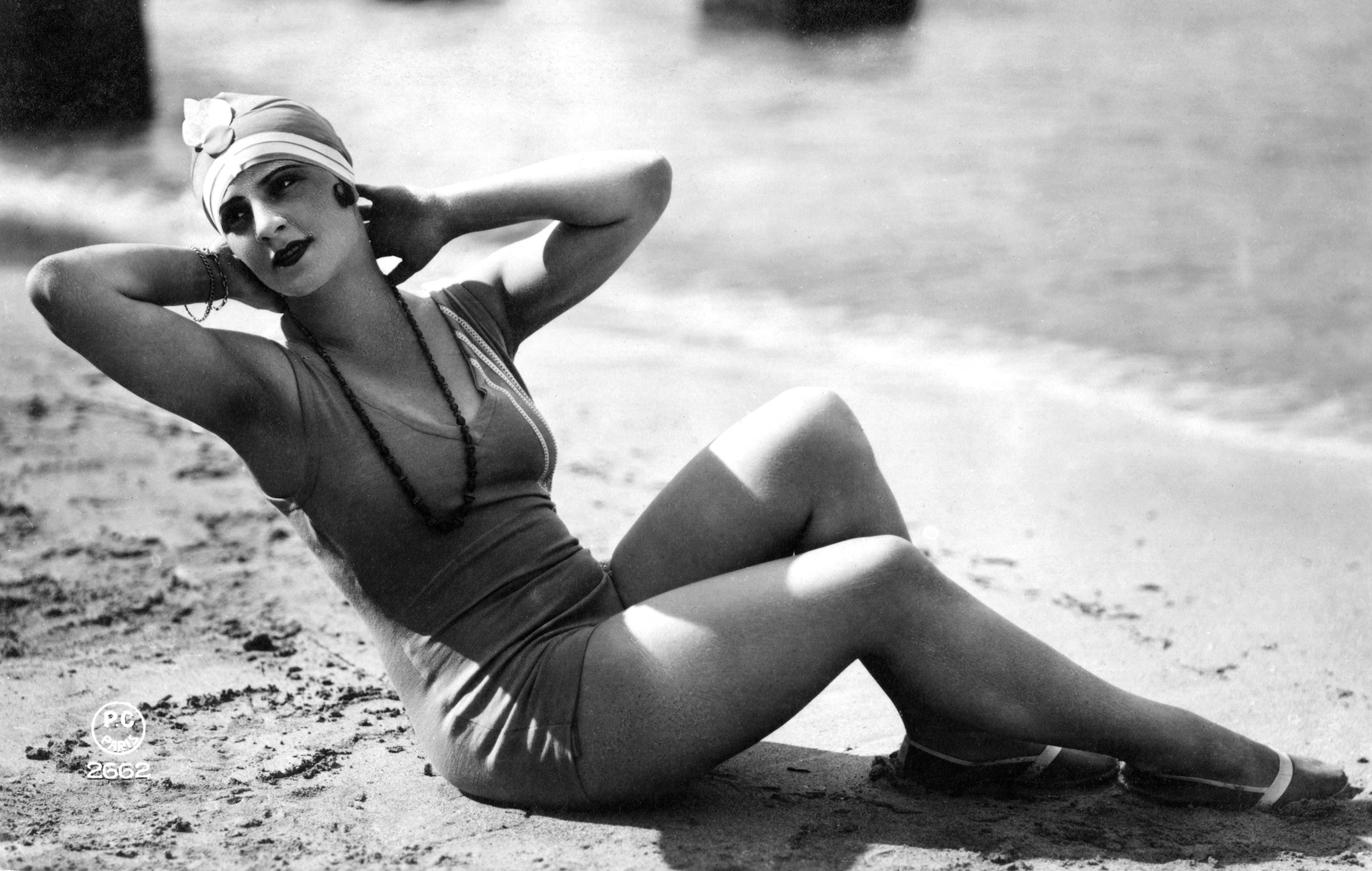 Woman in one-piece bathing suit and cap reclining on a beach in France, circa 1900.