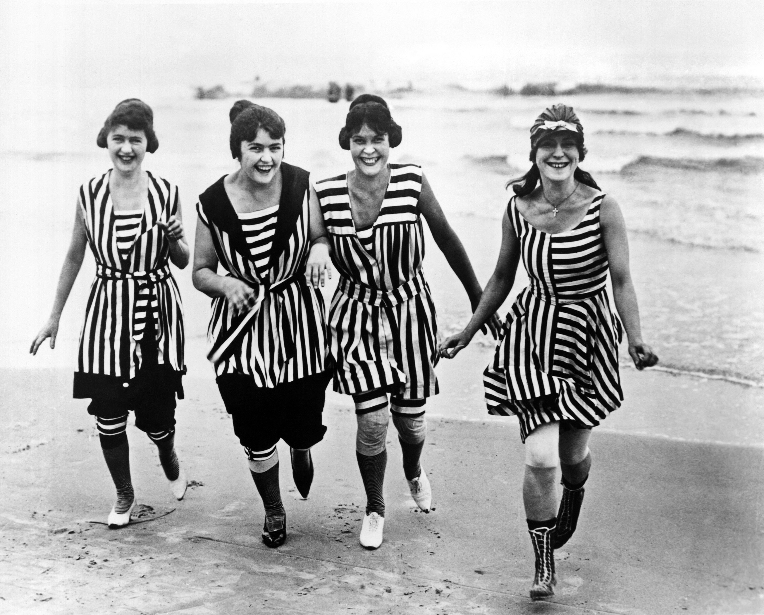 Four young women in matching beach wear run out of the surf, Los Angeles, circa 1910.