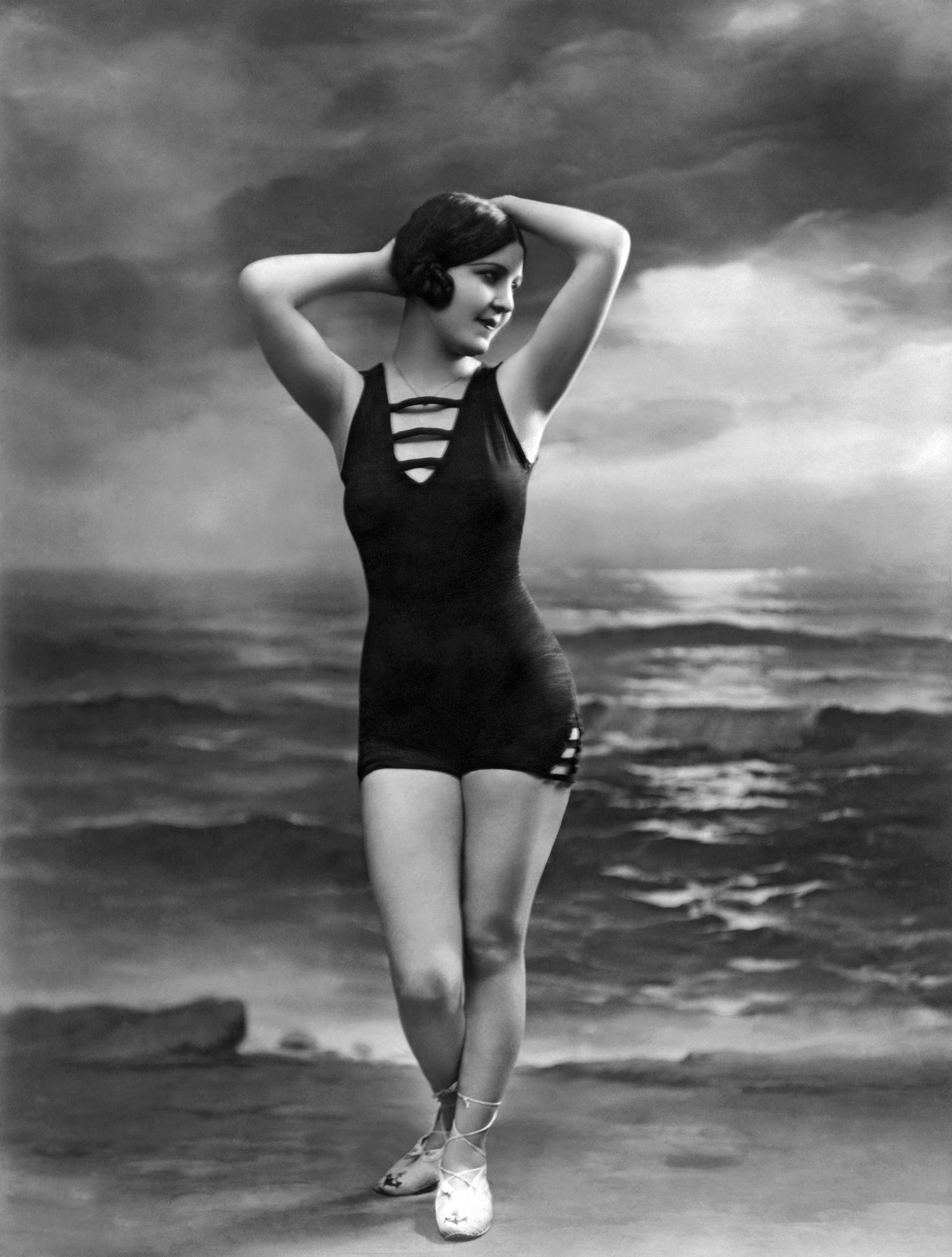 A woman in a bathing suit poses in front of a studio ocean scene, Paris, France, circa 1920.