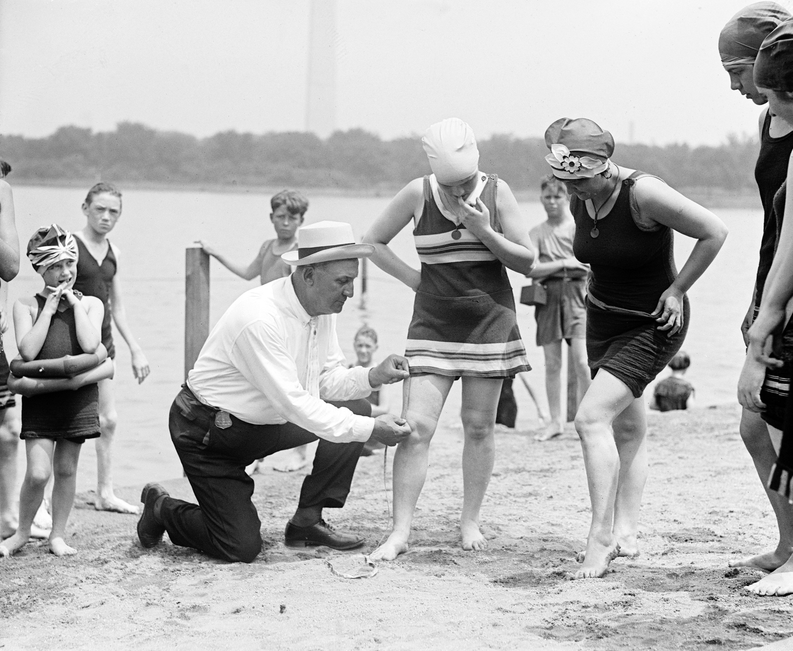 Woman having her swimsuit measured for length violations on a Washington DC beach, circa 1922.