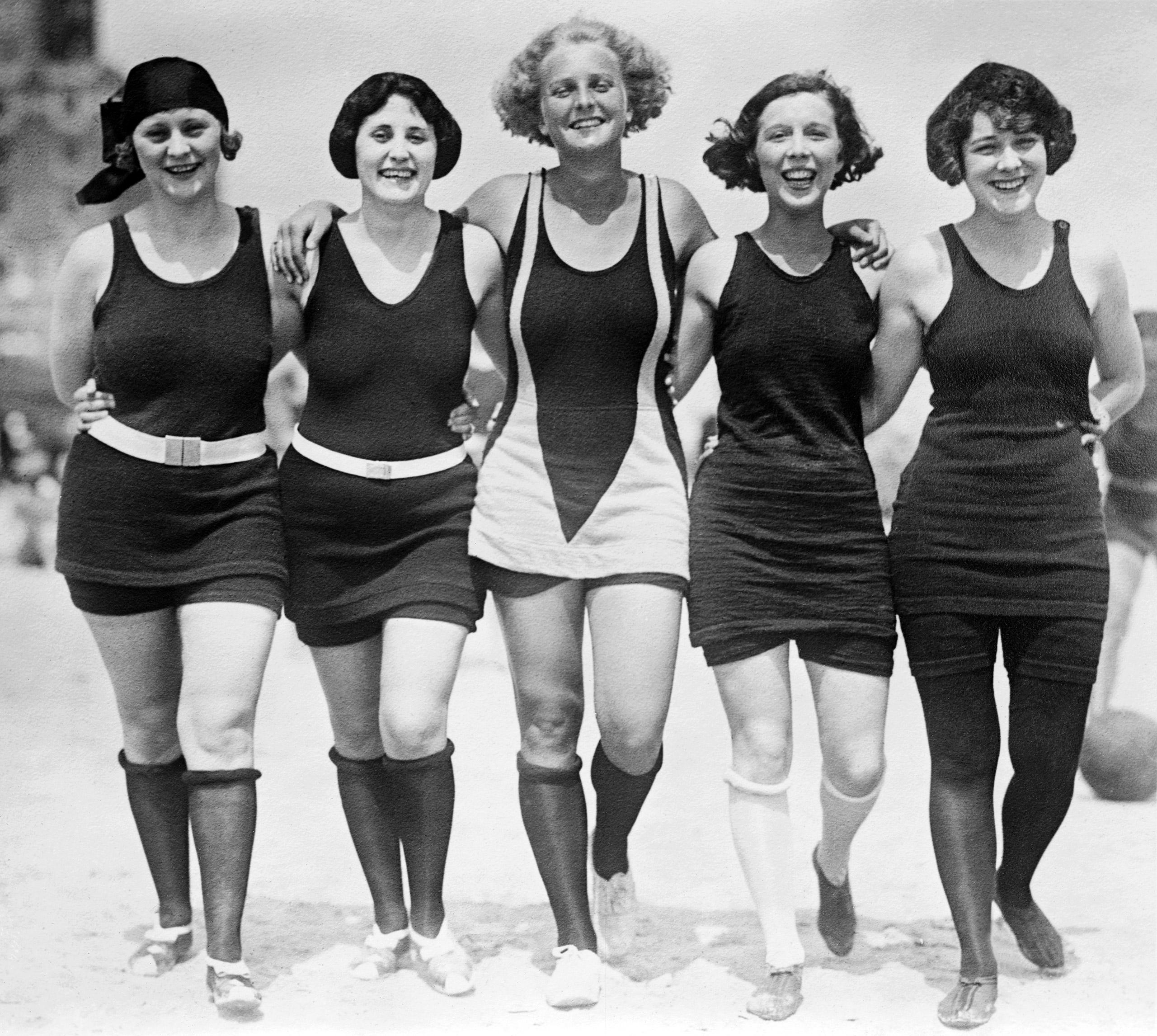 Five women walking arm-in-arm on the beach wearing wool bathing suits, circa 1925.