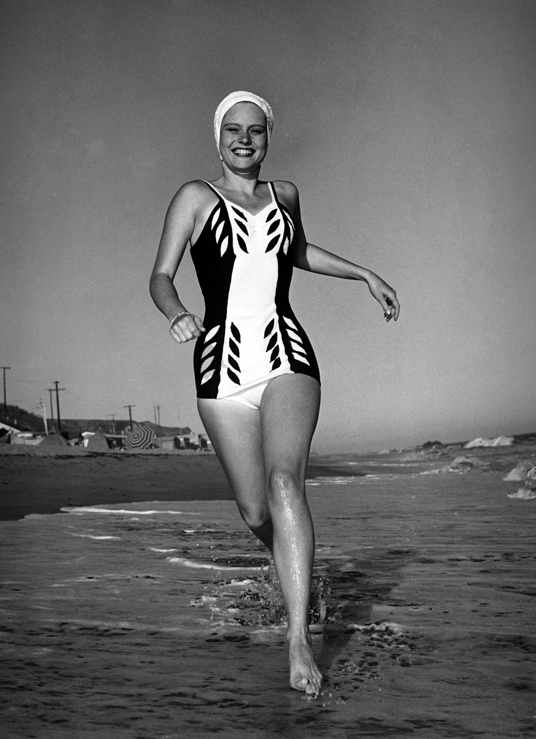 Actress Alexis Smith in a swimming costume running along the beach in southern California, circa 1940.