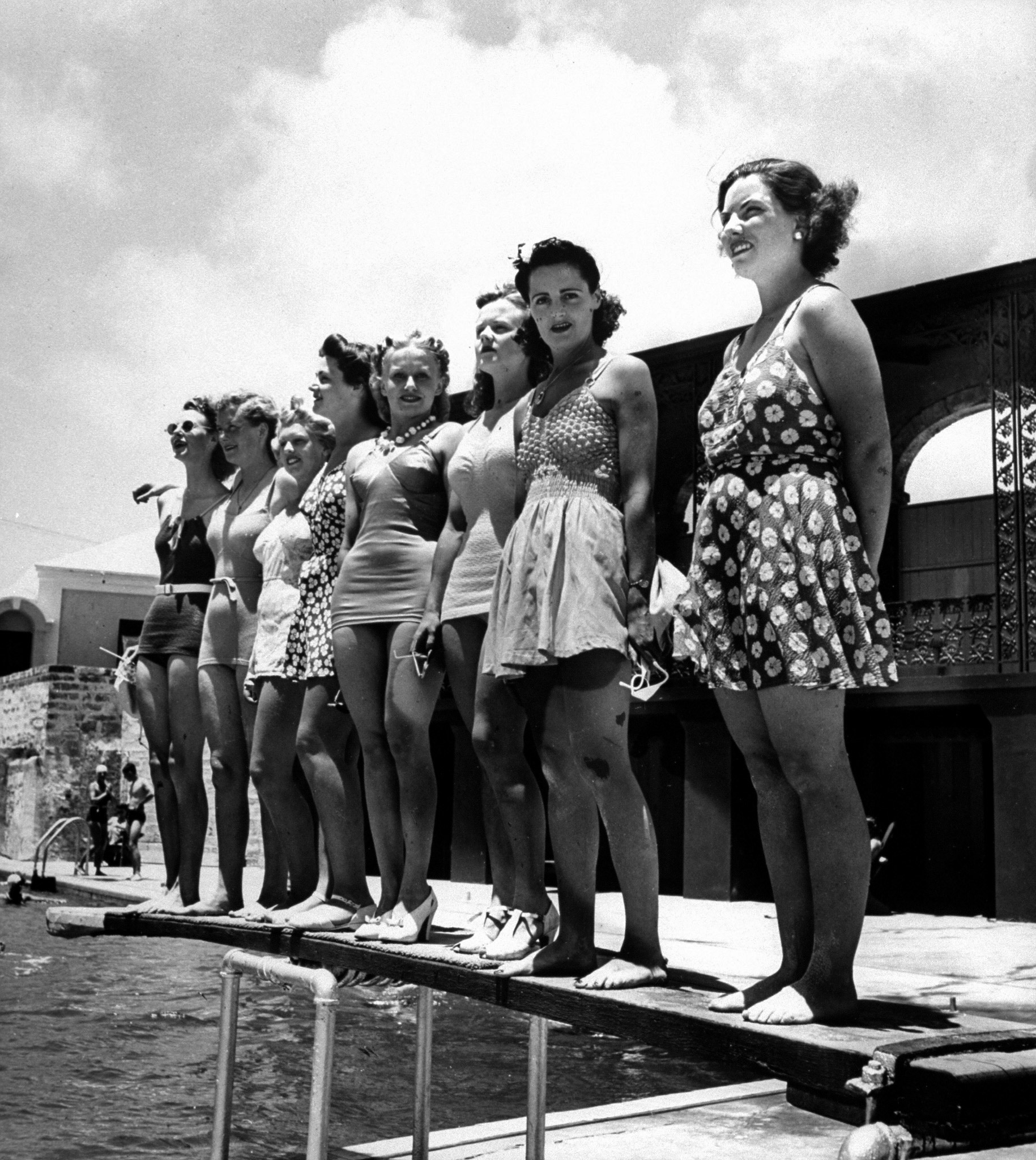 Bathing suit clad female members of the British Imperial Censorship Staff, who call themseleves the censorettes, standing poolside at the Princess Hotel, which also serves as their offices on the island. Circa 1941.
