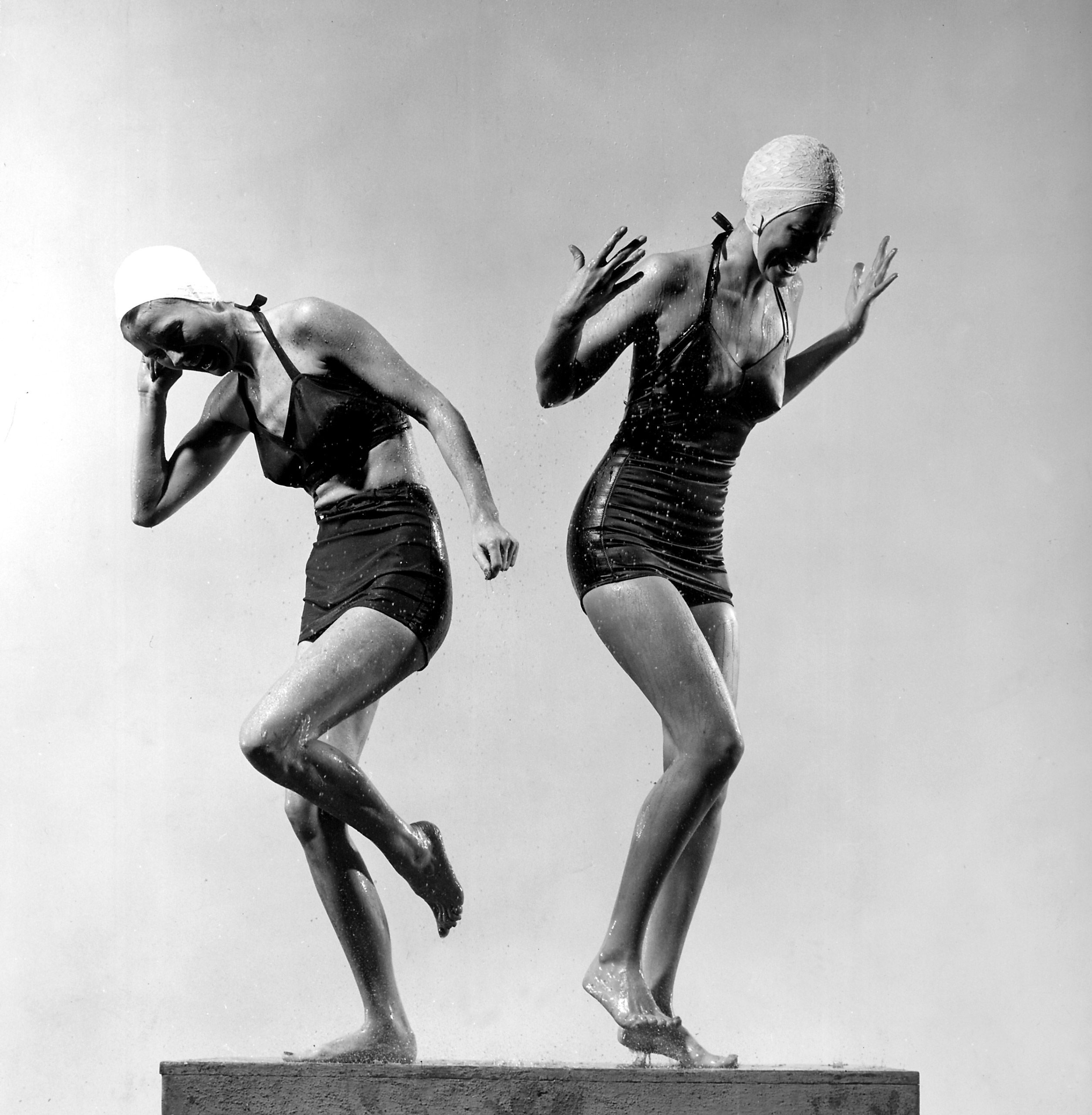 Two models wearing bathing suits and bathing caps, circa 1946.