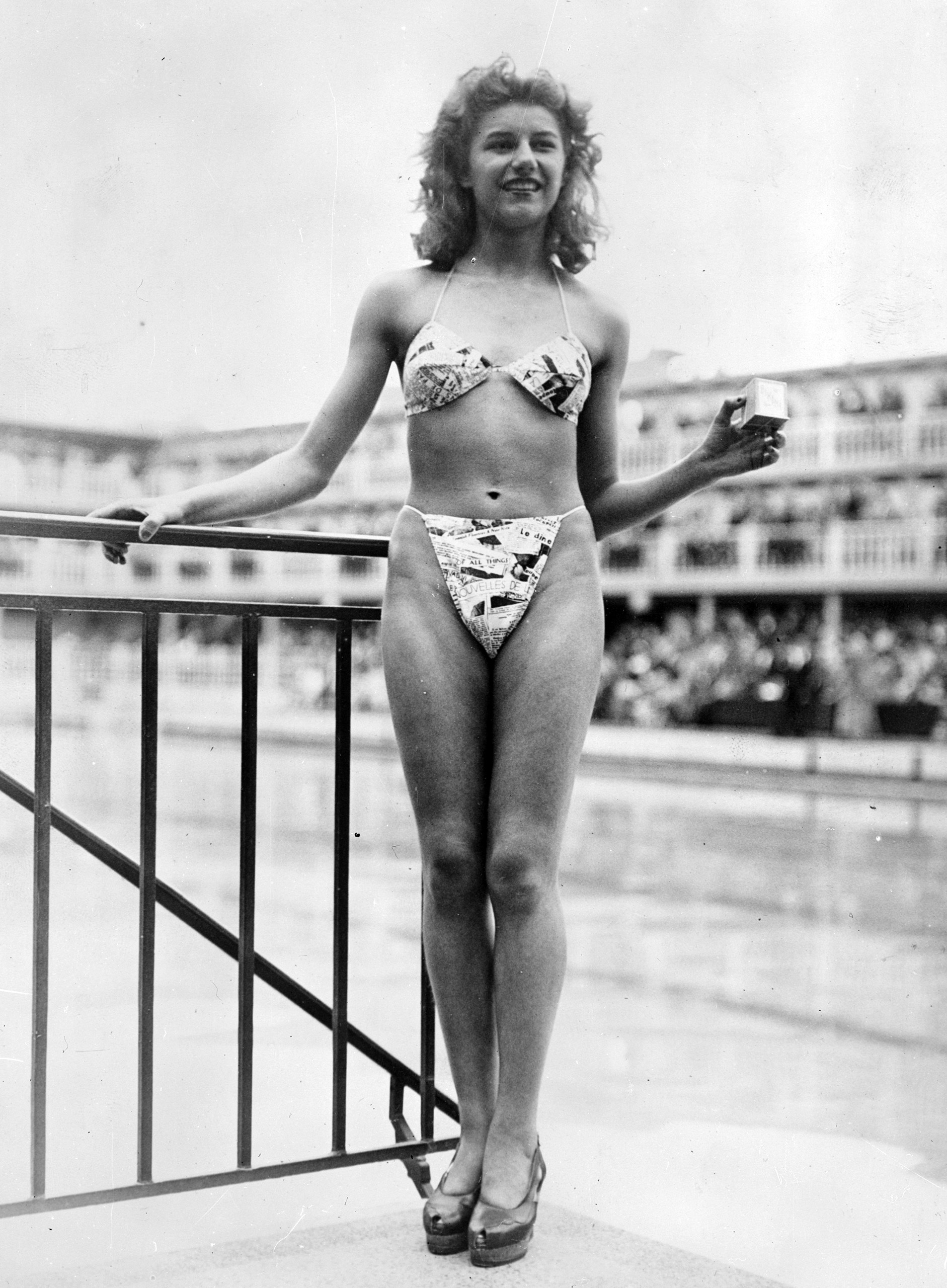 The new 'Bikini' swimming costume caused a sensation at a beauty contest at the Molitor swimming pool in Paris. Designer Louis Reard was unable to find a 'respectable' model for his costume and the job of displaying it went to 19-year-old Micheline Bernardini, a nude dancer from the Casino de Paris. She is holding a small box into which the entire costume can be packed. Celebrated as the first bikini, Luard's design came a few months after a similar two-piece design was produced by French designer Jacques Heim.