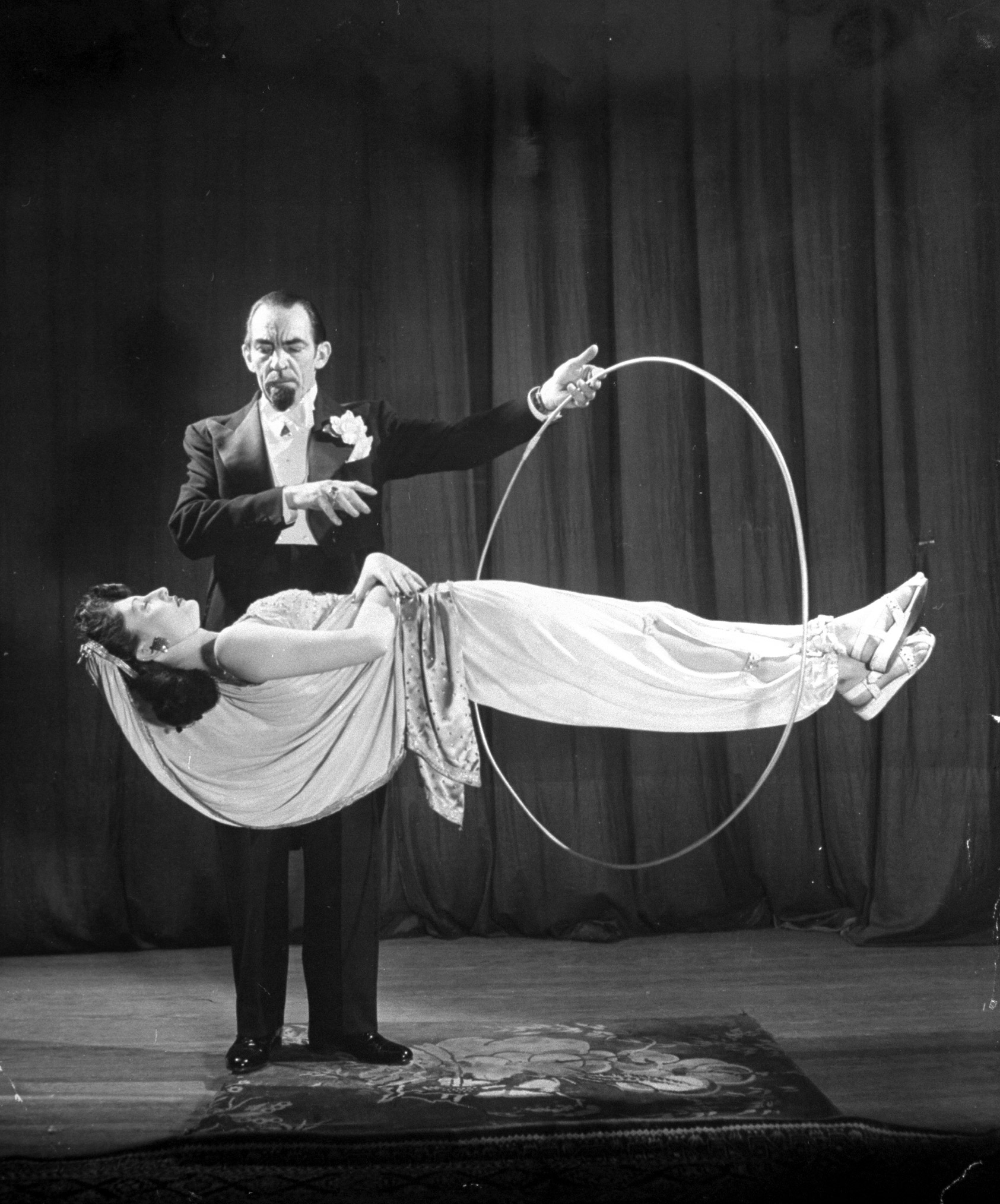Caption from LIFE. Best new trick at convention was variation of the famous old levitation act. Its inventor, Jack Gwynne, pretends first to hypnotize his daughter-in-law Helen. Then he stretches her across two sawhorses, finally removes the supports entirely so that Helen is seemingly suspended in mid-air. Gwynne passes a hoop completely over her body to show that there is no support. Gwynne tells nobody how it is done and few magicians at the convention could guess.