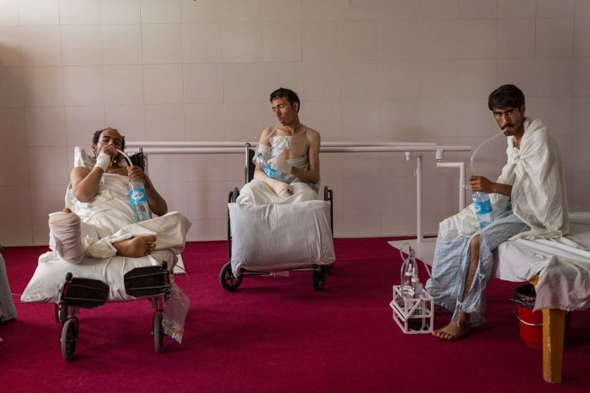Patients with chest injuries strengthen their lung capacity with water bottles in the physical therapy room at the Emergency hospital in Lashkar Gah, Afghanistan on March 27, 2015.