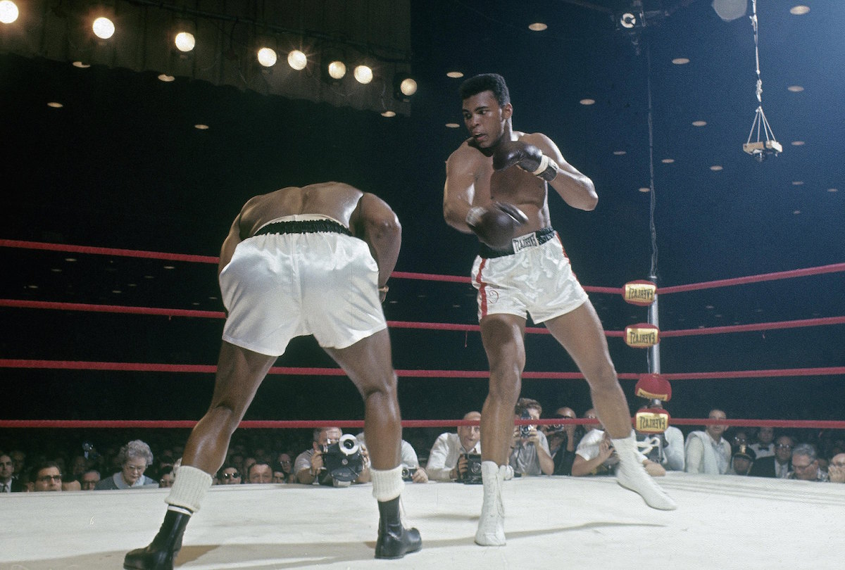 The boxer then known as Cassius Clay (R) throws a punch at Sonny Liston (L) in a World Heavyweight Title fight Feb. 25, 1964 at Convention Hall in Miami