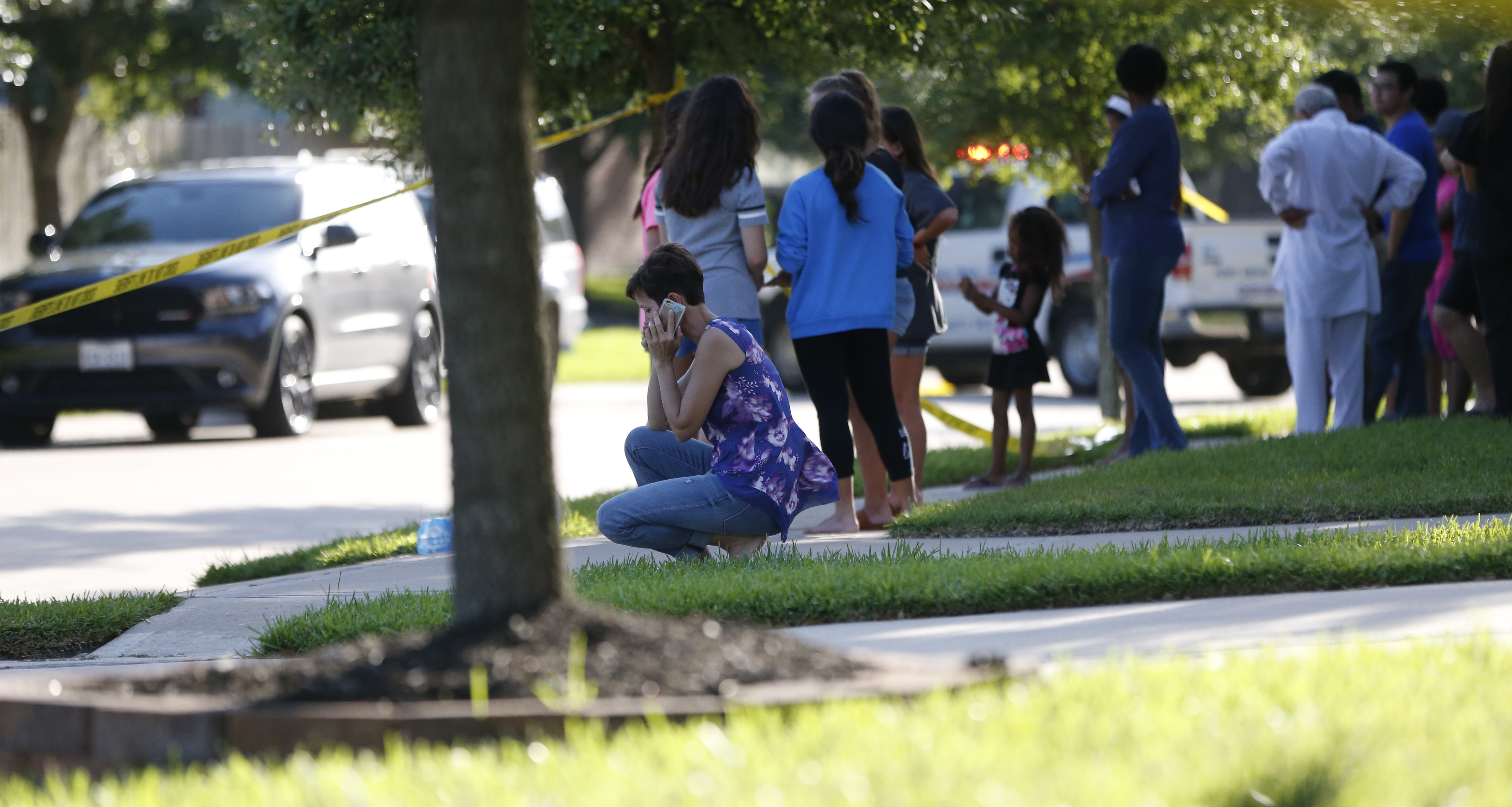 Neighbors gather to watch as Fort Bend County Sheriffs department investigates a shooting in Katy, Texas on June 24, 2016.