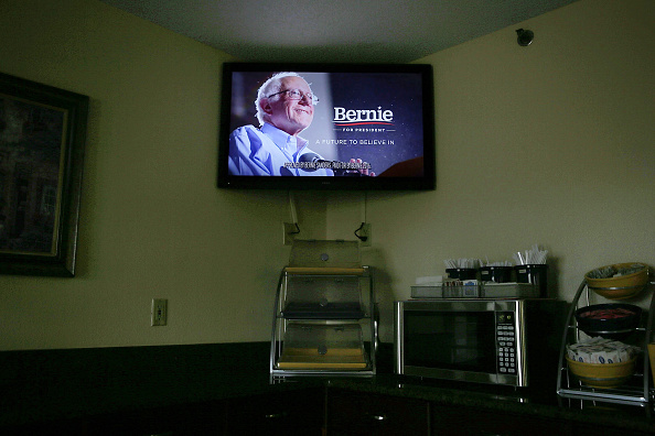 A campaign ad paid for by Democratic presidential candidate Sen. Bernie Sanders' campaign is shown on the TV in a hotel breakfast room November 16, 2015 in Des Moines, Iowa.