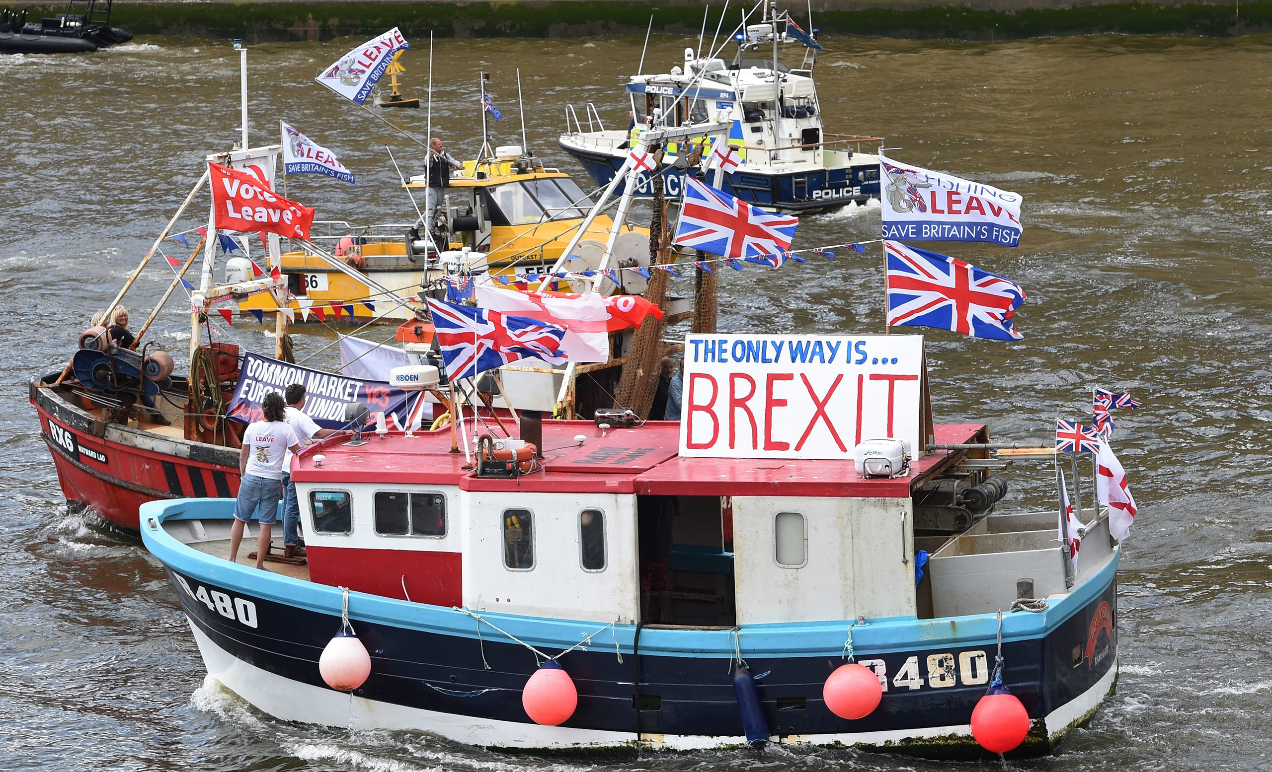 A flotilla of fishing trawlers, organized by UKIP leader Nigel Farage, sails up the river Thames next to the Houses of Parliament in London, June 15, 2016.