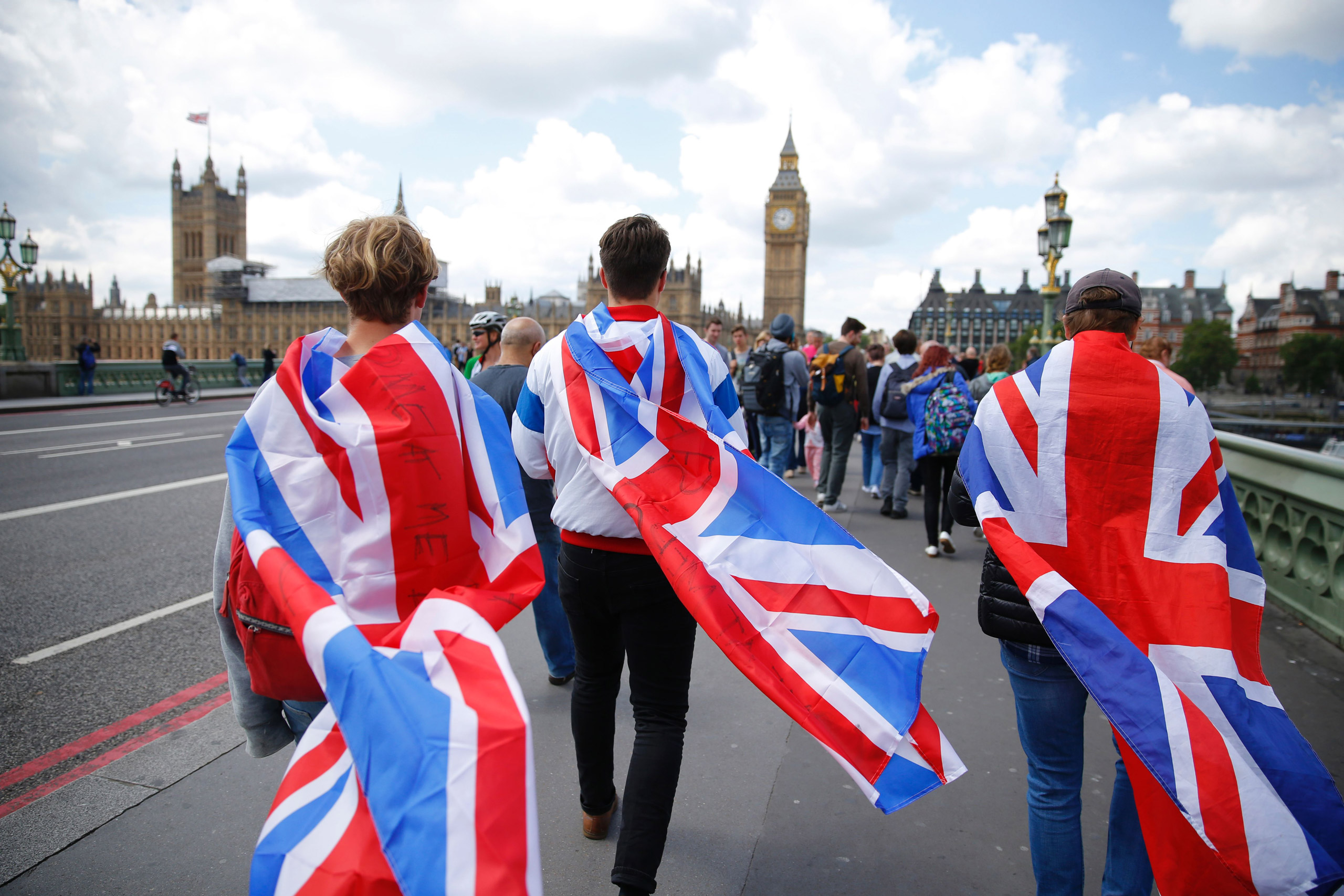 People walk over Westminster Bridge wrapped in Union flags in London on June 26, 2016.