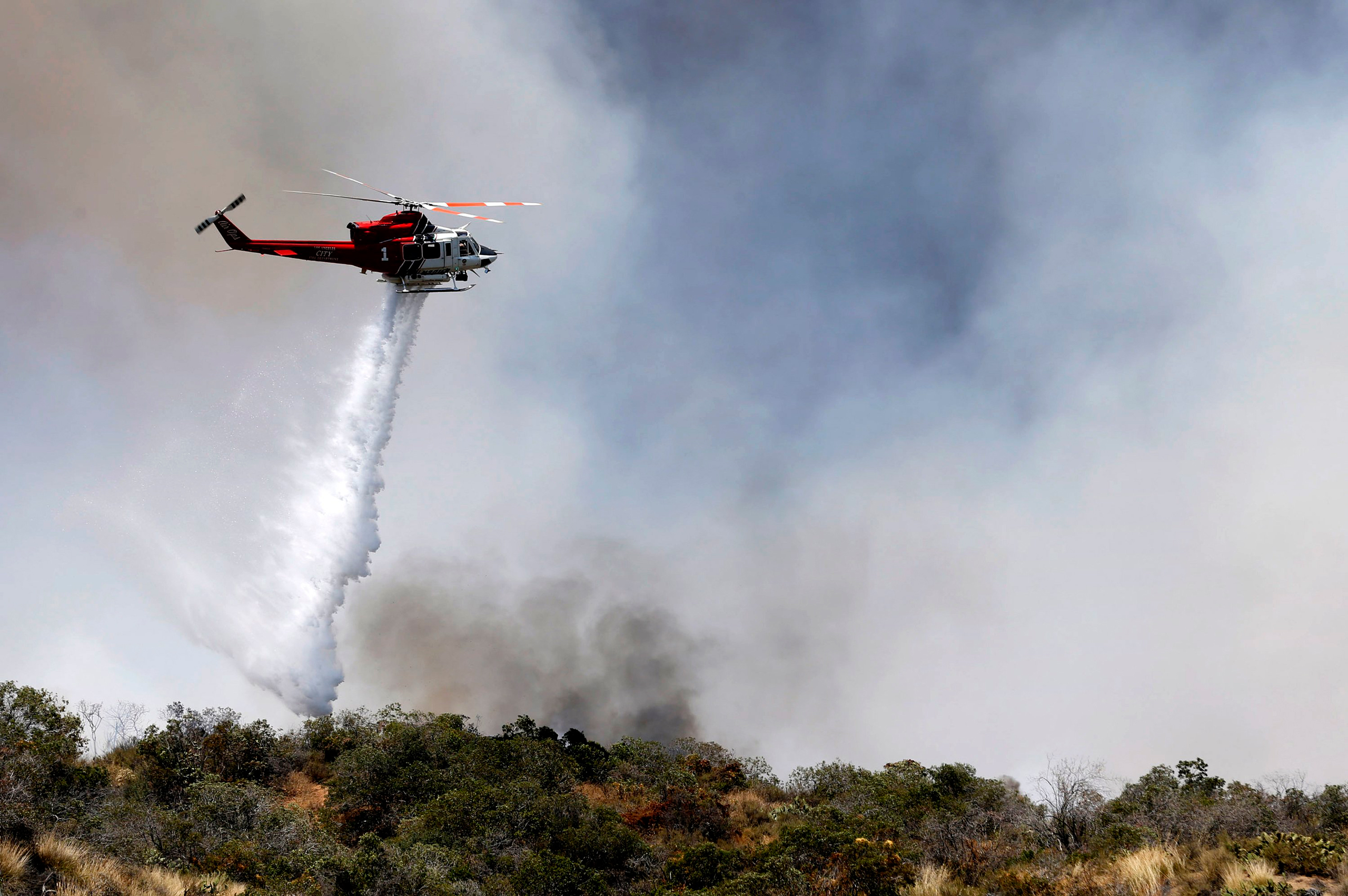 A firefighting helicopter makes a water drop over a wildfire just north of Azusa, Calif., on June 20, 2016.
