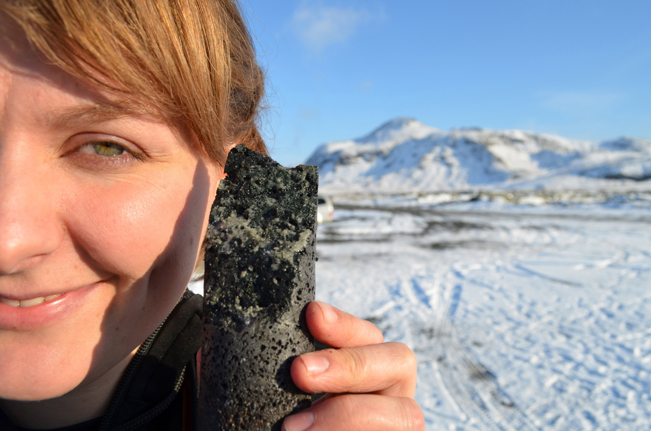 An experimental drill core held by coauthor Sandra Snaebjornsdottir in Iceland, laced with solidified carbonate, apparently produced by a new process that turns carbon emissions to stone when pumped underground.