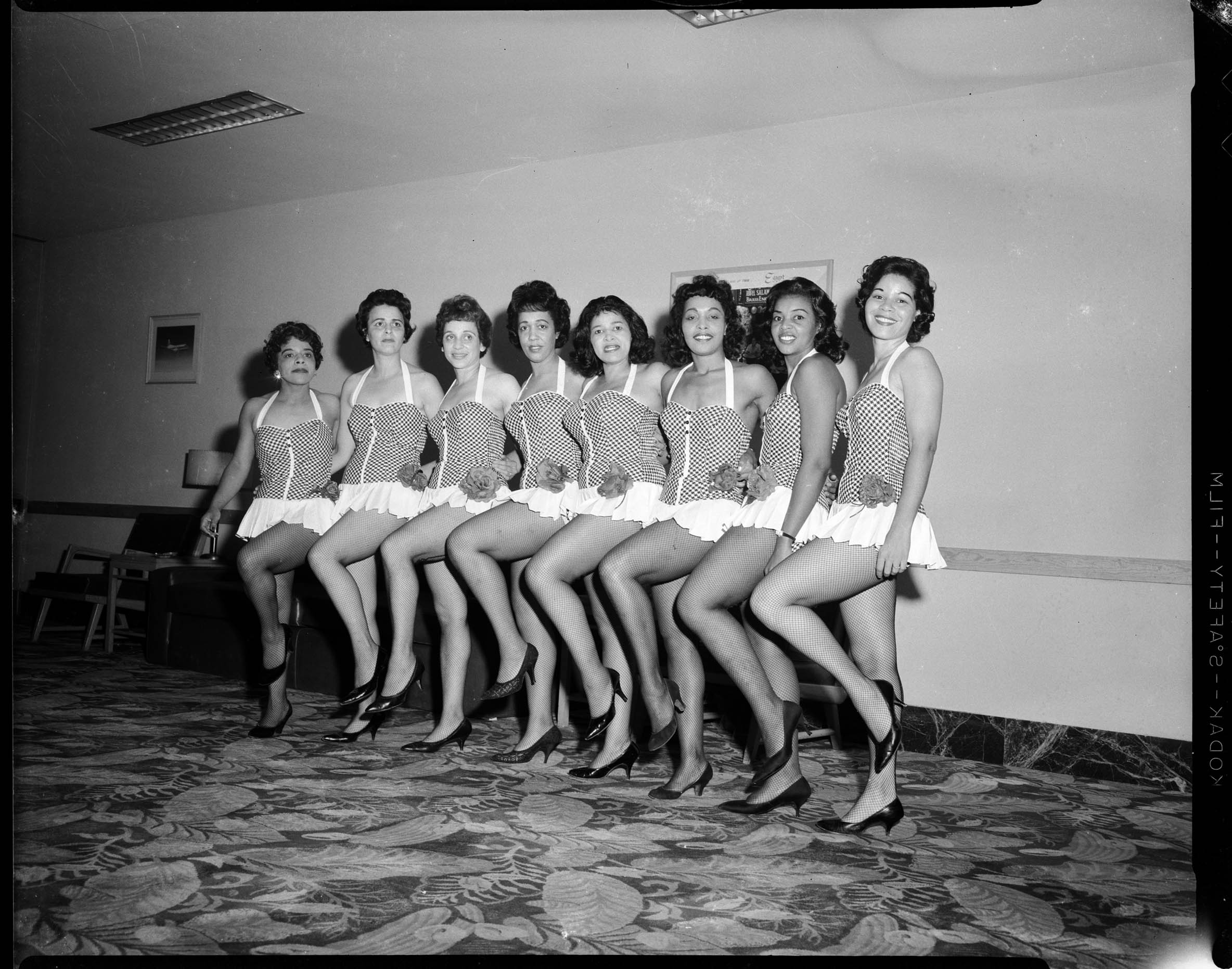 Members of Junior Mothers Association wearing dance costumes, from left: June Stokes, Dolores McCoy Taylor, Evelyn Anderson, Alma Speed Fox, Betty Tibbs, Lois Weaver Watson, Phyllis Pitts, and Frances Bell Nunn, posed in Horizon Room, Aug. - Sept. 1961.