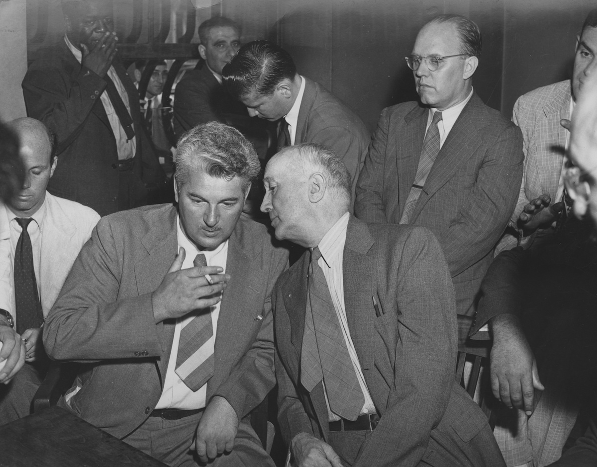 A group of American Communists, following their release on bail, July 1948. They are facing charges of conspiring to preach the overthrow of the government, under the Smith Act. In the foreground, Eugene V. Dennis (left) listens to William Z. Foster.