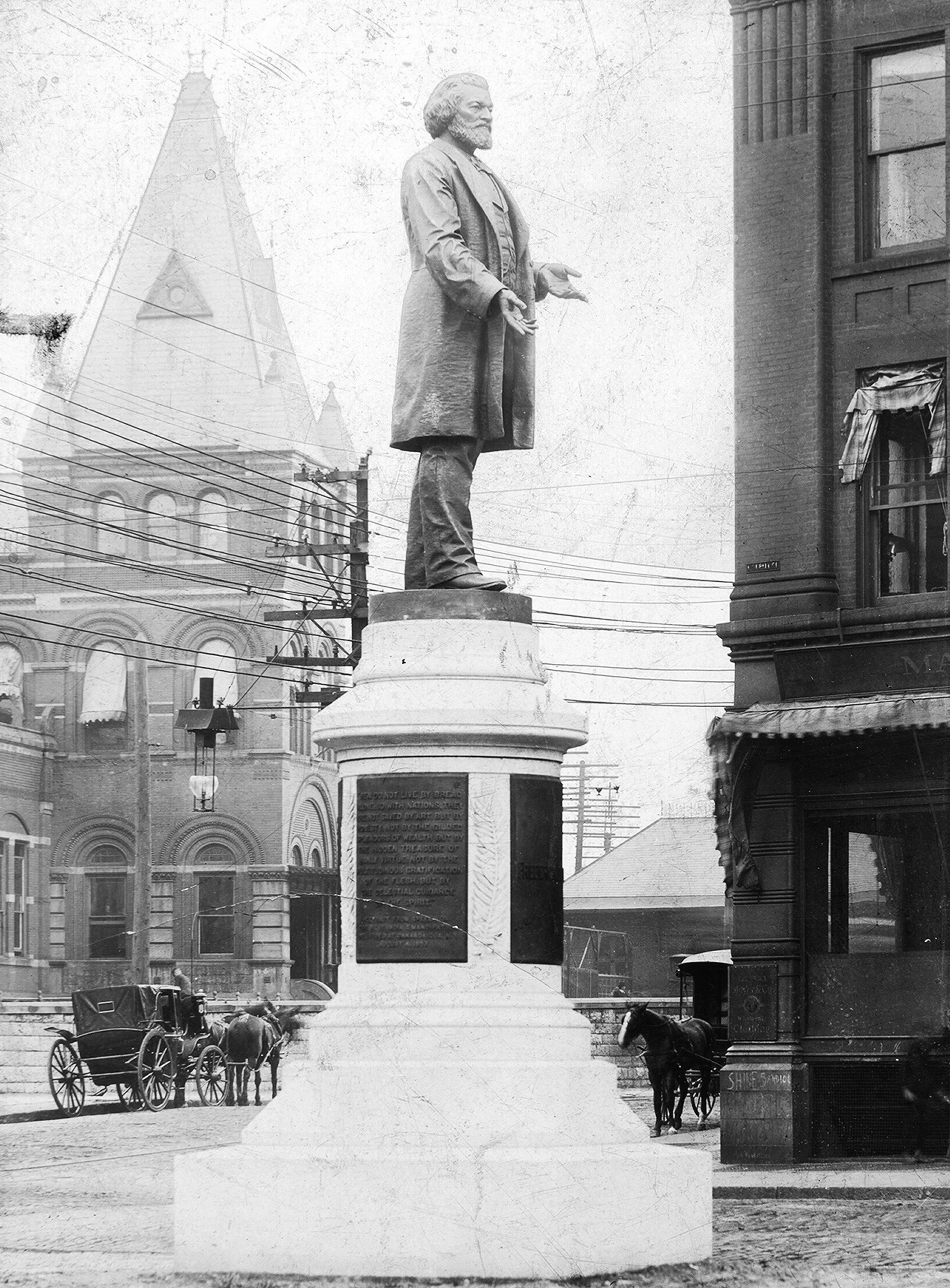 A monument built to honor Frederick Douglass, a statue of Douglass stands on top of a stone base in Rochester, New York, 1900.