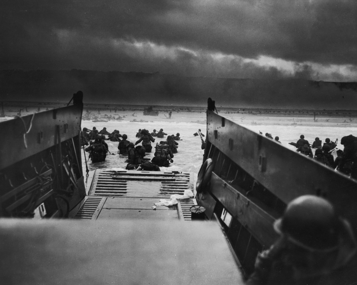 A view from inside one of the landing craft after US troops hit the water during the Allied D-Day invasion of Normandy, France. The US troops on the shore are lying flat under German machine gun resistance.