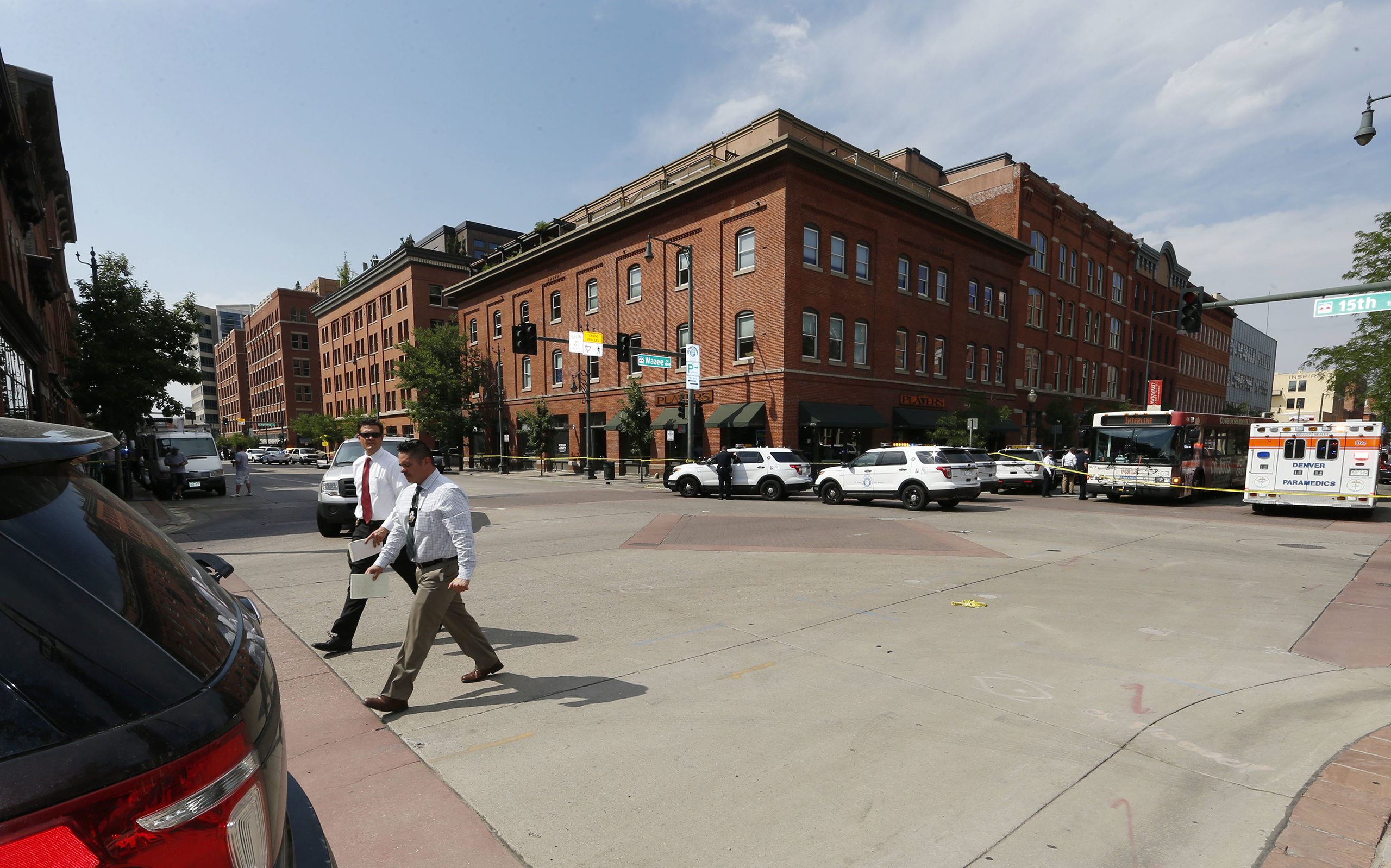 Investigators walk through the intersection of 15th Street and Wazee near the scene of a shooting in a lower downtown business in Denver on June 28, 2016.