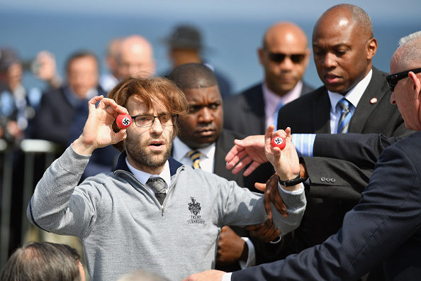 Comedian Lee Nelson is taken away by security while holding golf balls stamped with swastika as he protests against Presumptive Republican nominee for US president Donald Trump a he gave a press conference on the 9th tee at his Trump Turnberry Resort on June 24, 2016 in Ayr, Scotland.