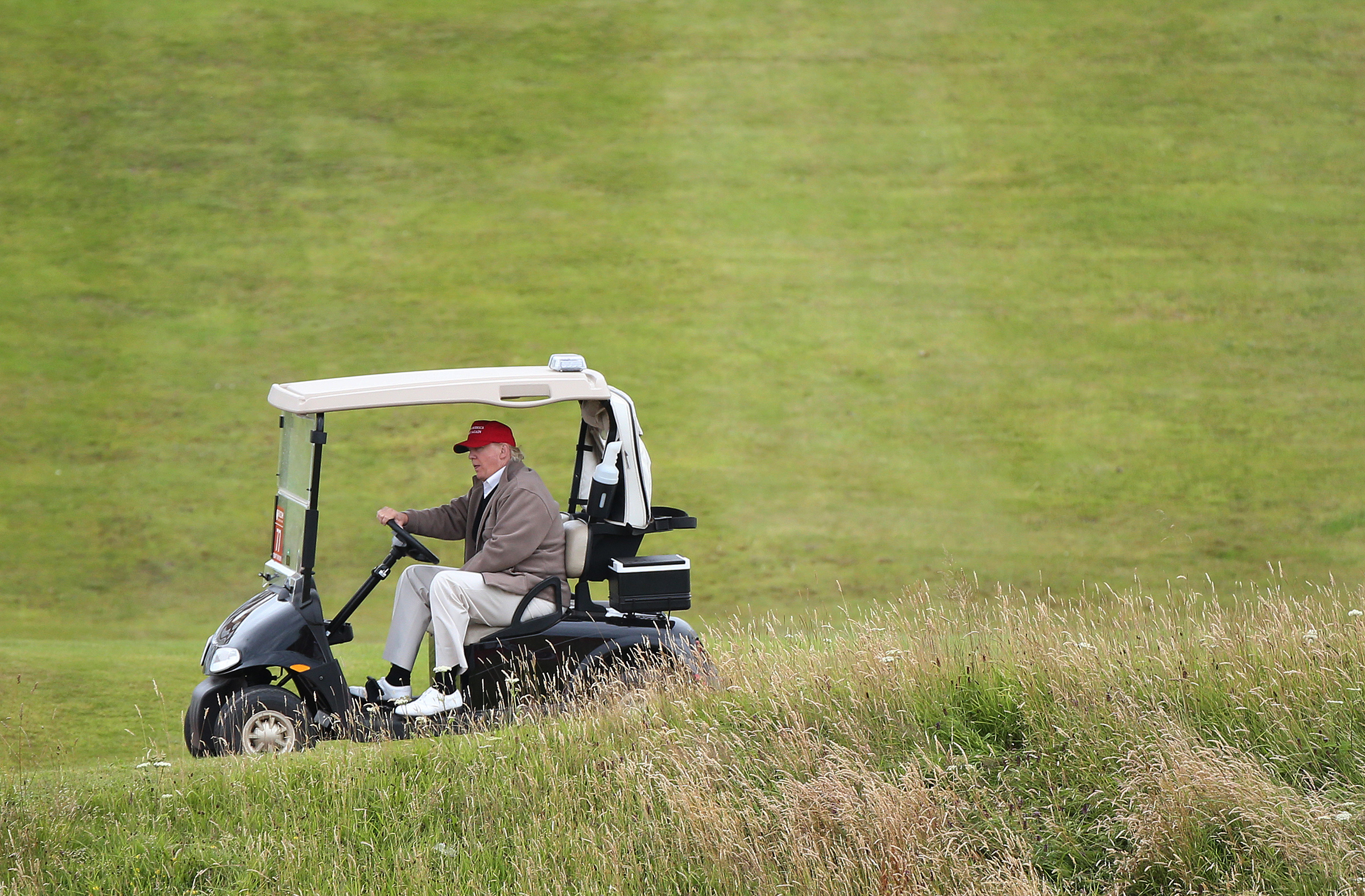 Donald Trump drives his golf buggy during the second day of the 2015 Women's British Open golf championship on the Turnberry golf course in Scotland.