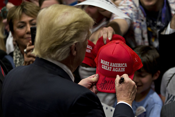 Donald Trump, president and chief executive of Trump Organization Inc. and 2016 Republican presidential candidate, signs a campaign hat after speaking during a campaign rally at West Chester University in West Chester, Pennsylvania, U.S., on Monday, April 25, 2016.