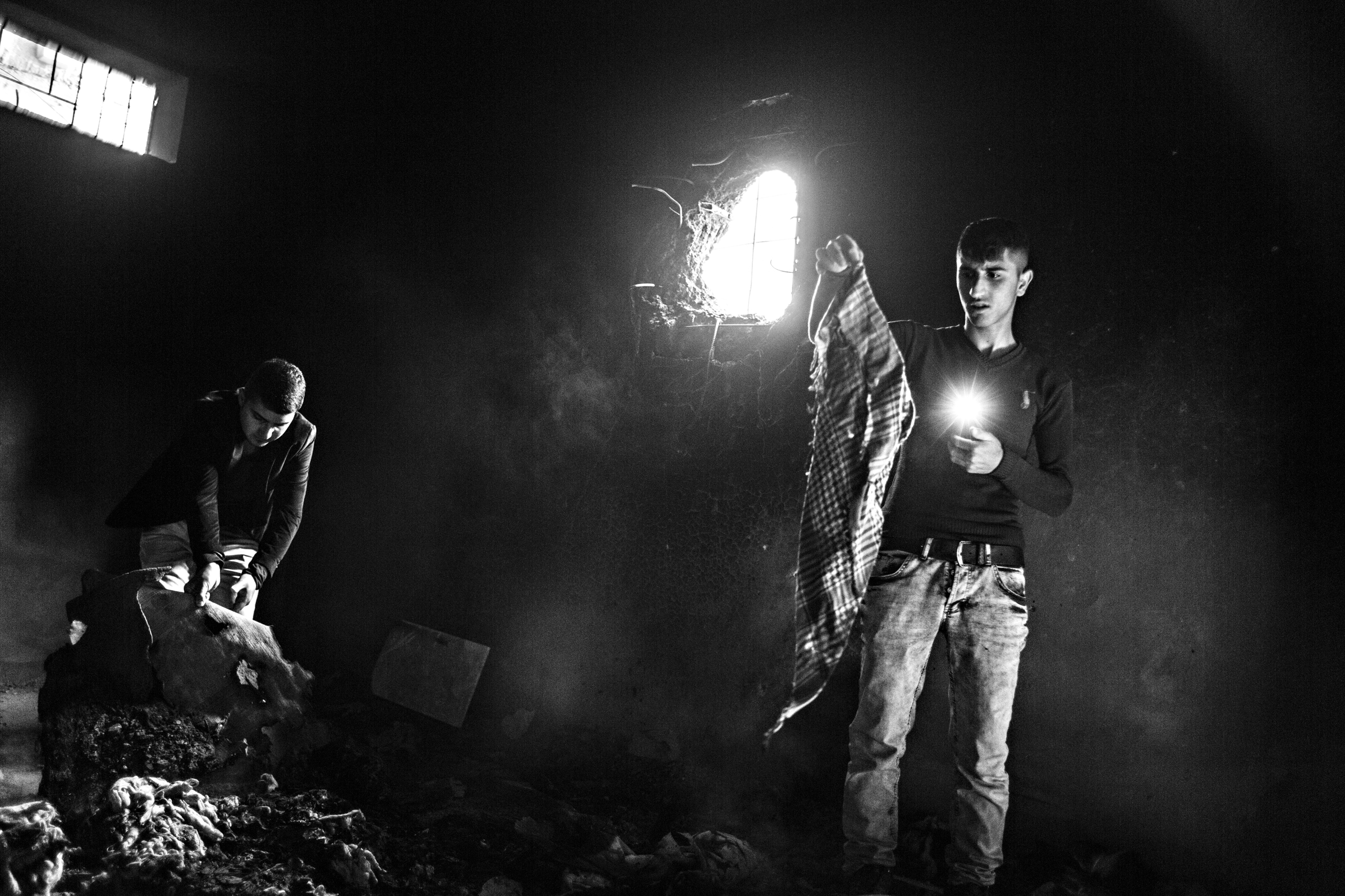 Men investigate a basement where 28 people were killed by Turkish special forces, Cizre, March 2016.
