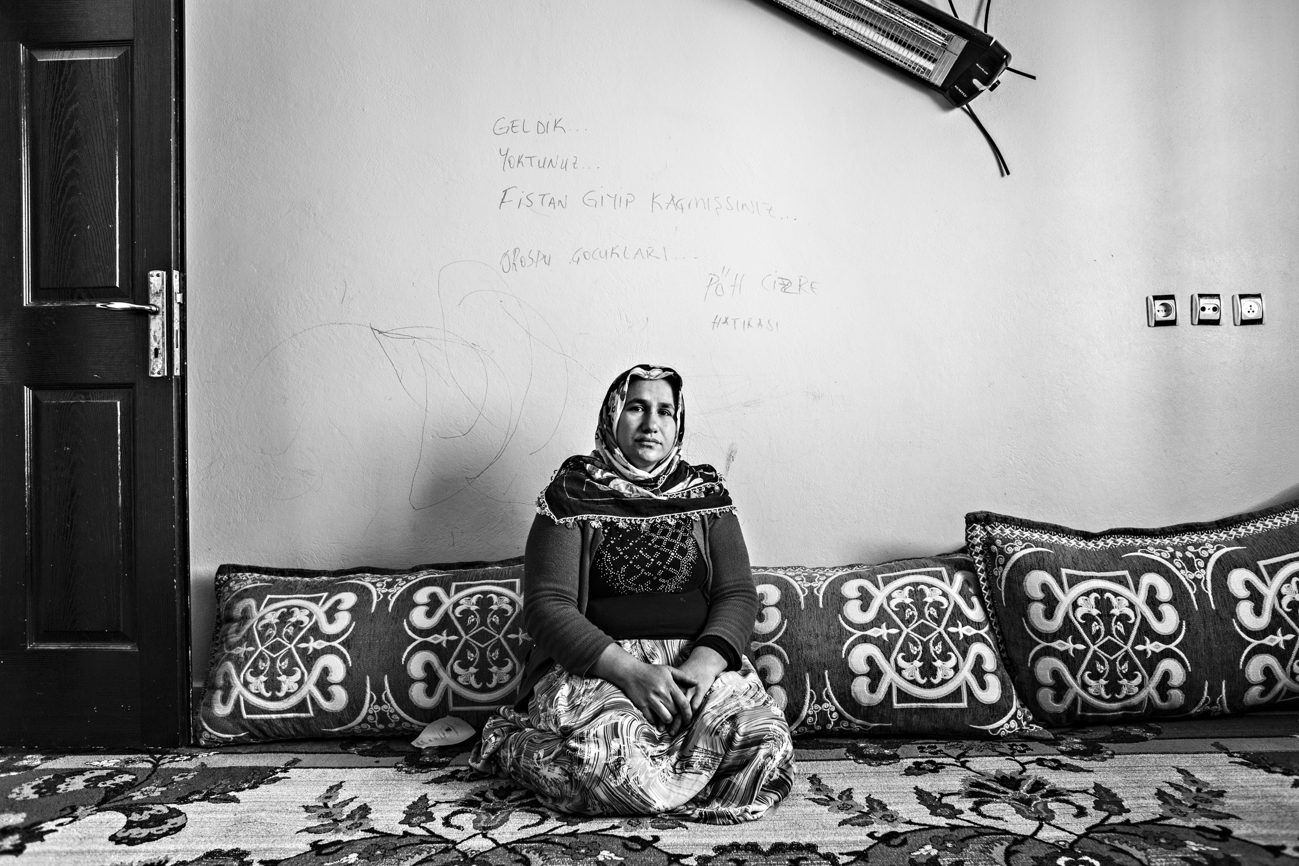 Fatma Tetik sits near a wall with threatening graffiti written by Turkish special forces.  Her husband, Ali Tetik, was killed during fighting between Turkish special forces and PKK (Kurdistan Workers Party), Cizre, March 2016.