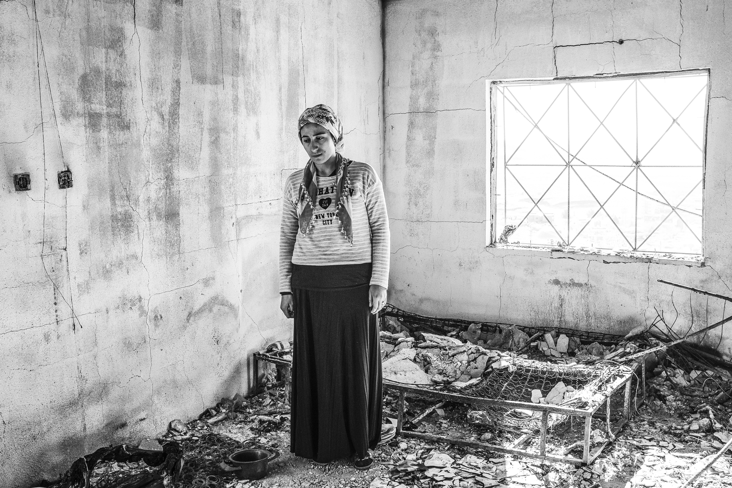 Zahide Onen stands in the wreckage of her home that was hit by a  Turkish military rocket, while she and her family slept, Derik, Turkey, Dec. 2015.