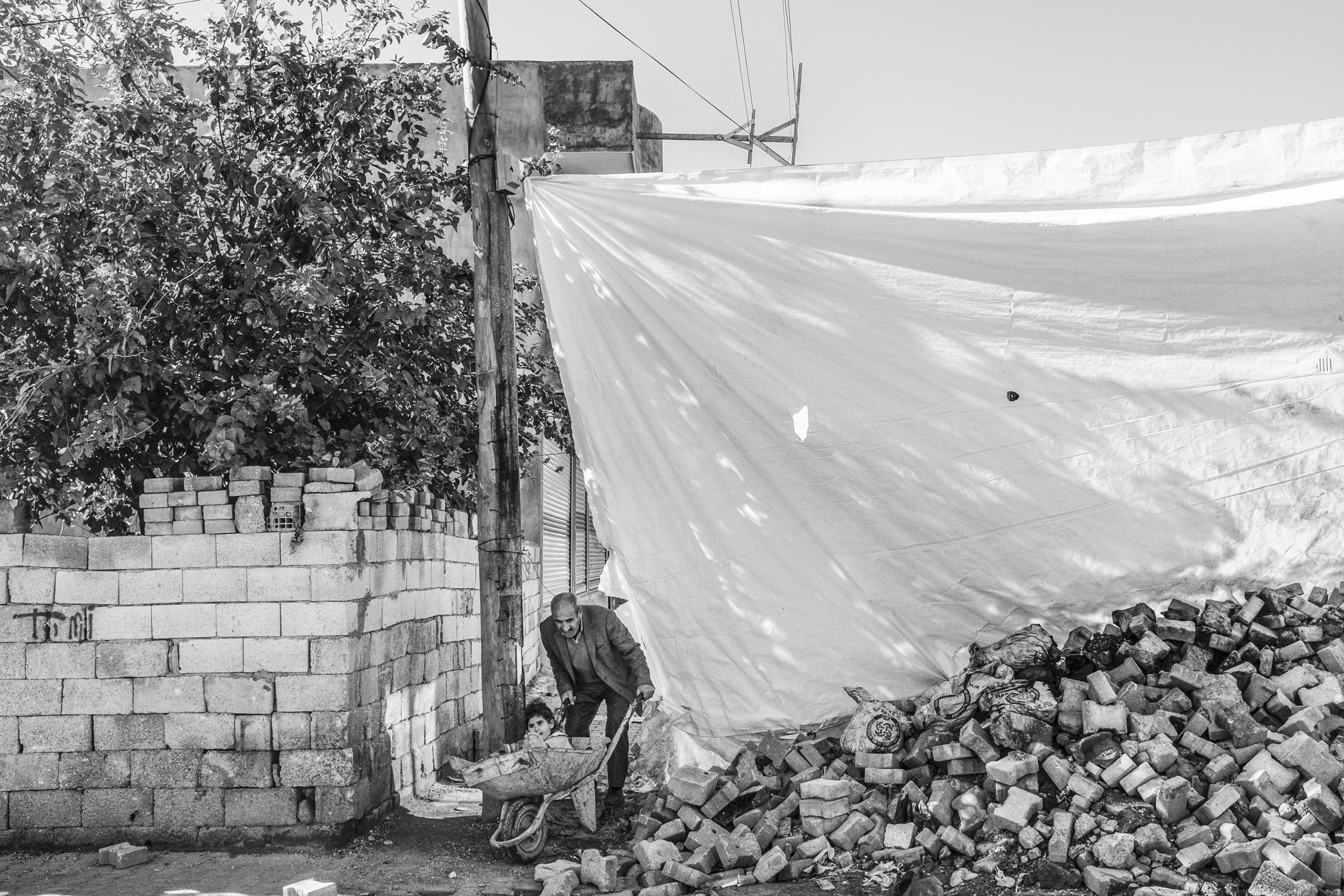 Walking past a make-shift barricade, a man carries his daughter to the hospital in a wheelbarrow, Nusaybin, Turkey, Dec. 2015.