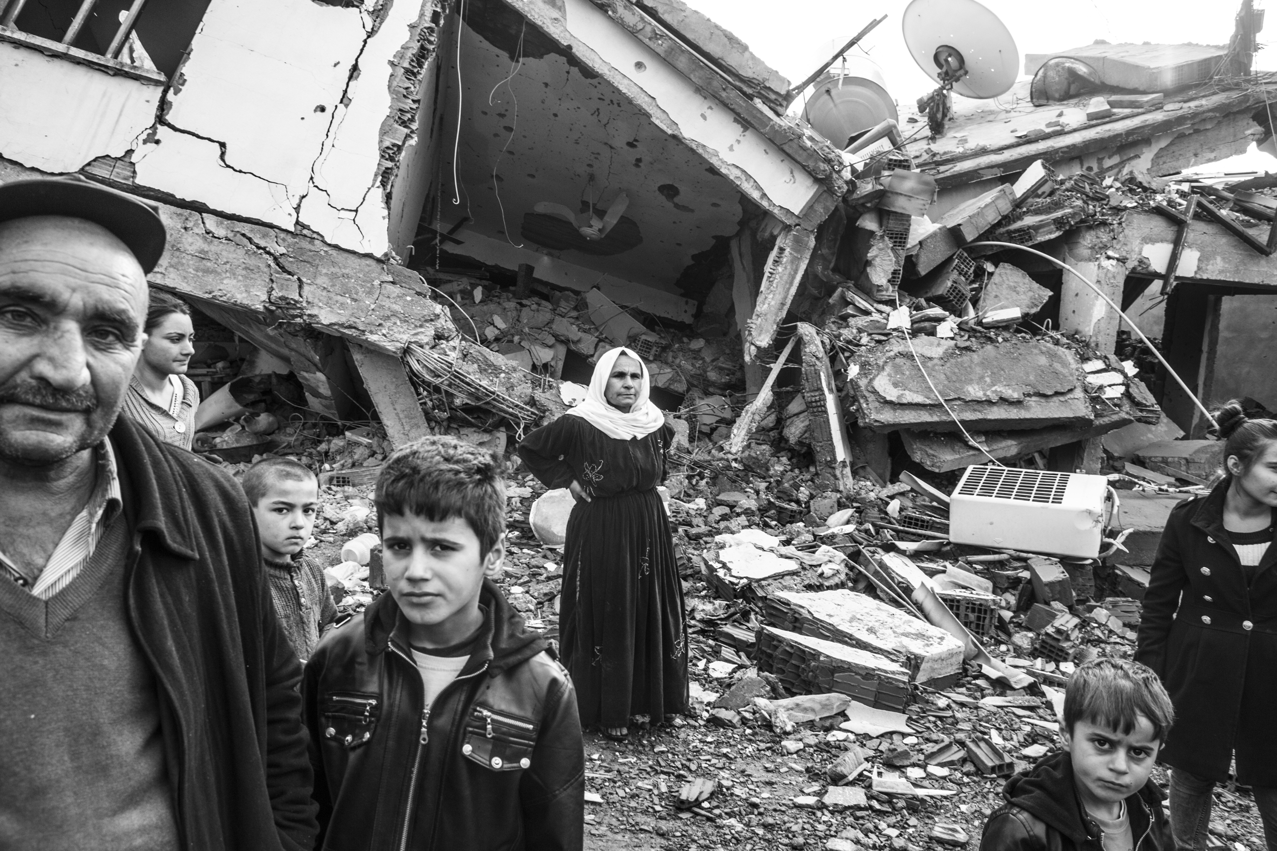 A family stands near their home that was damaged during fighting between government troops and separatist Kurdistan Workers Party (PKK) fighters, in the Kurdish town of Silopi, near the border with Iraq, Jan. 2016