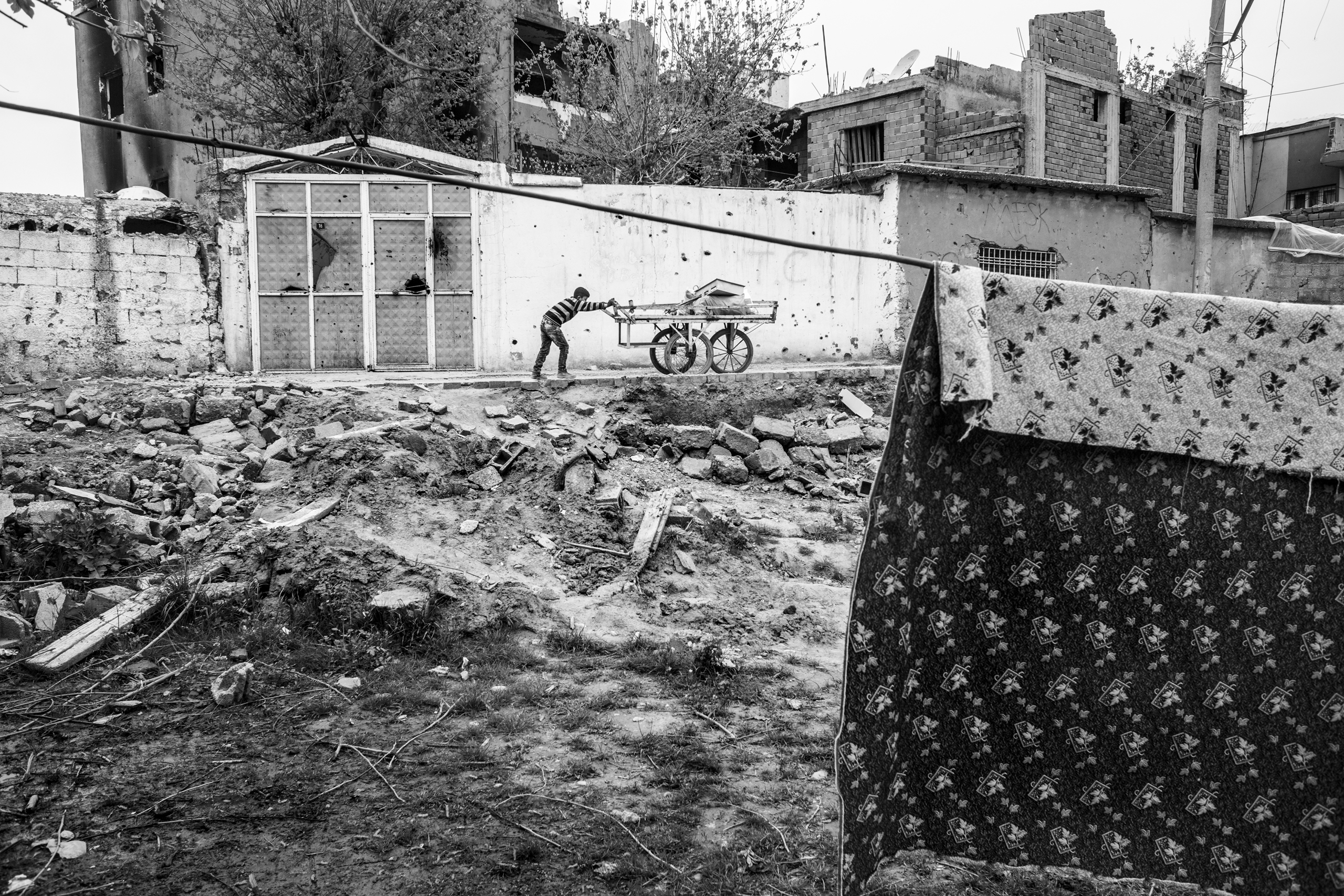 A child carries metal scraps in the ruins of Cizre, southeastern Turkey. The city was ht hard during the curfew imposed by the Turkish government in an attempt to suppress militants, March 2016.