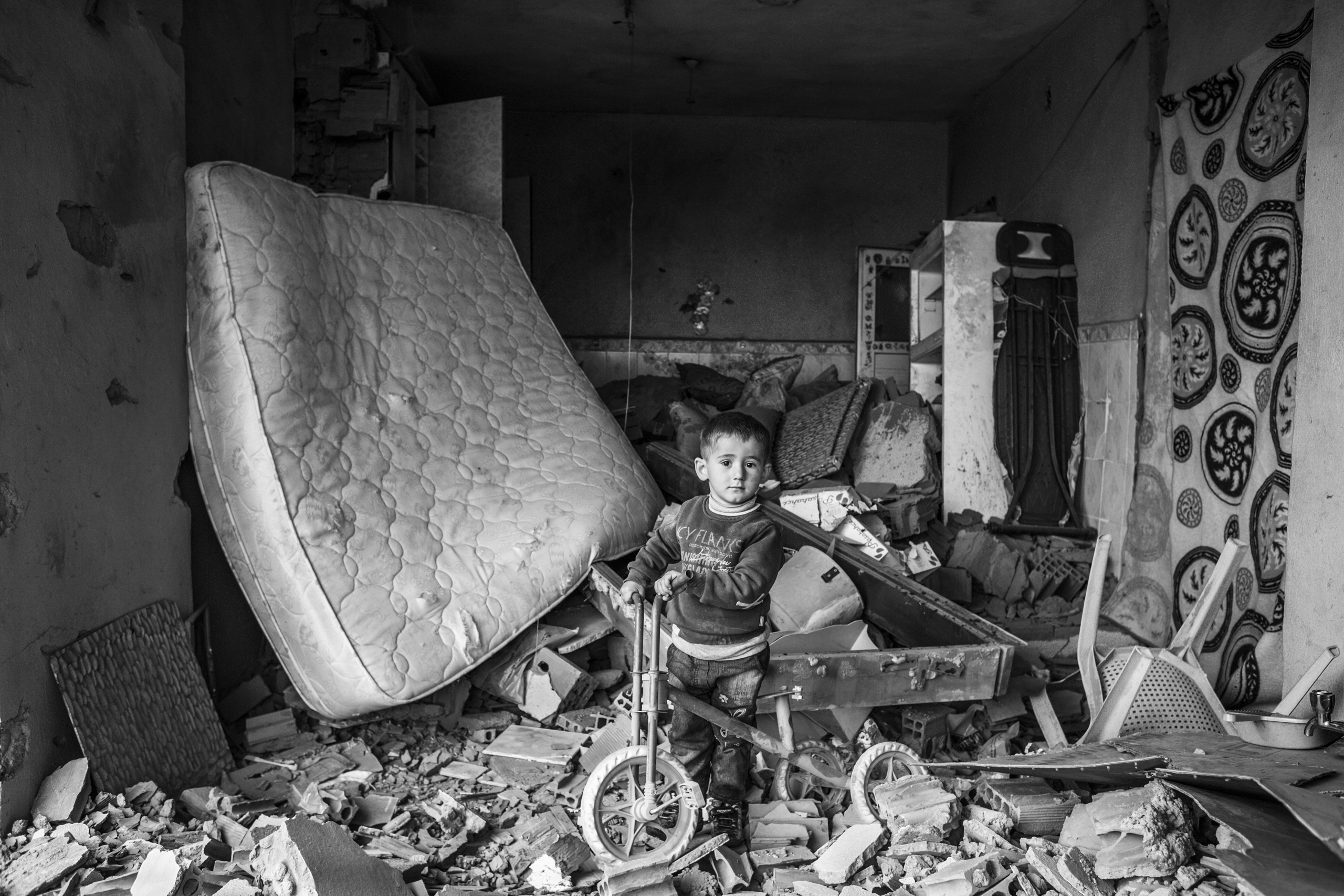 A child plays in his house that was damaged during fighting between government troops and separatist Kurdistan Workers Party (PKK) fighters, in the Kurdish town of Silopi, southeastern Turkey, near the border with Iraq, Jan. 2016.