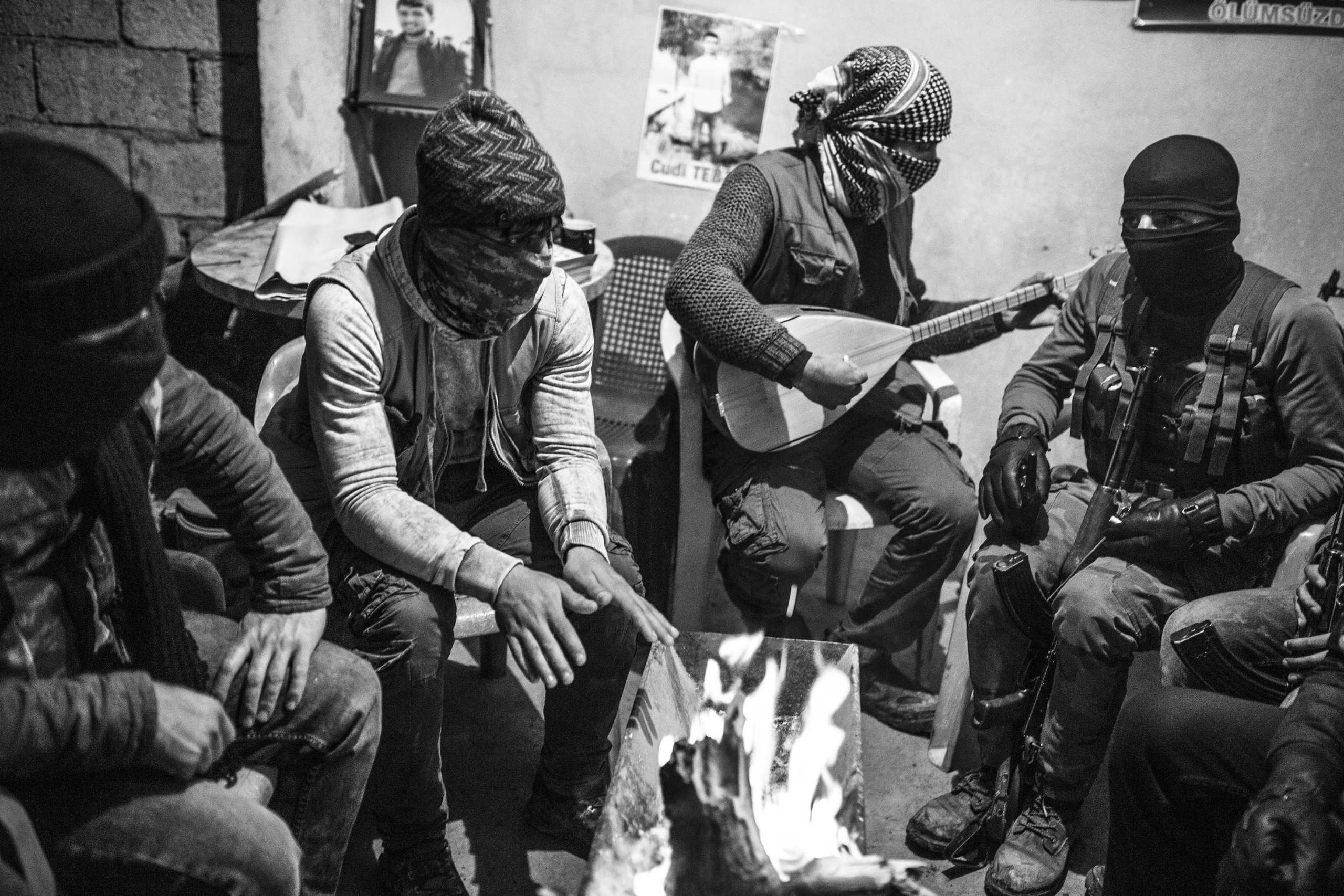 Members of the Civil Protection Units (YPS), a  Kurdish rebel group, warm up and play music near a fire in the YPS headquarters in Nusaybin, Turkey, Jan. 2016. The YPS was formed at the end of 2015 as a result of curfews imposed by the Turkish security forces and increased clashes.
