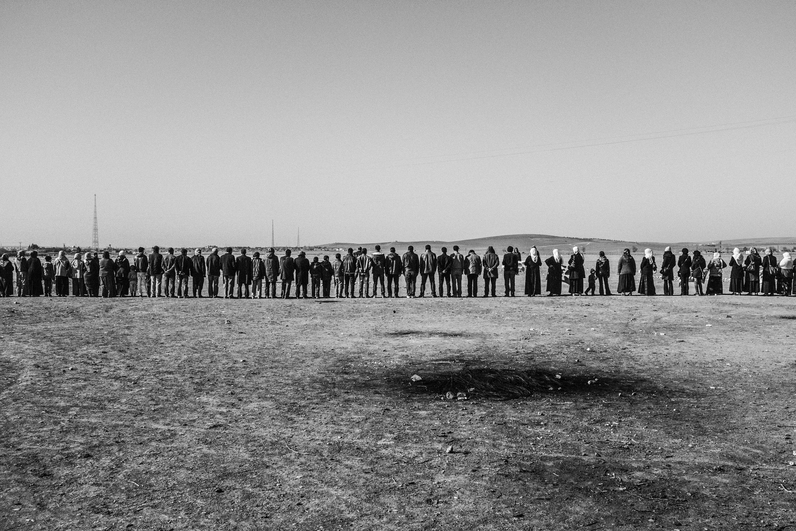 Refugees from Kobani, Syria line up at the Turkish-Syrian border  in Suruc, Turkey to support the Kurds fighting against ISIS, Jan. 2015