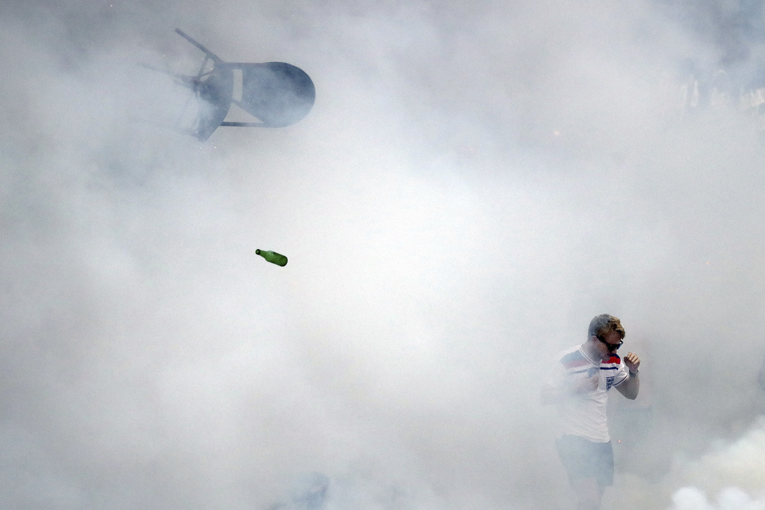 A bottle and chair are thrown as an England fan walks through tear gas as England fans clash with police in Marseille, France, on June 10, 2016.