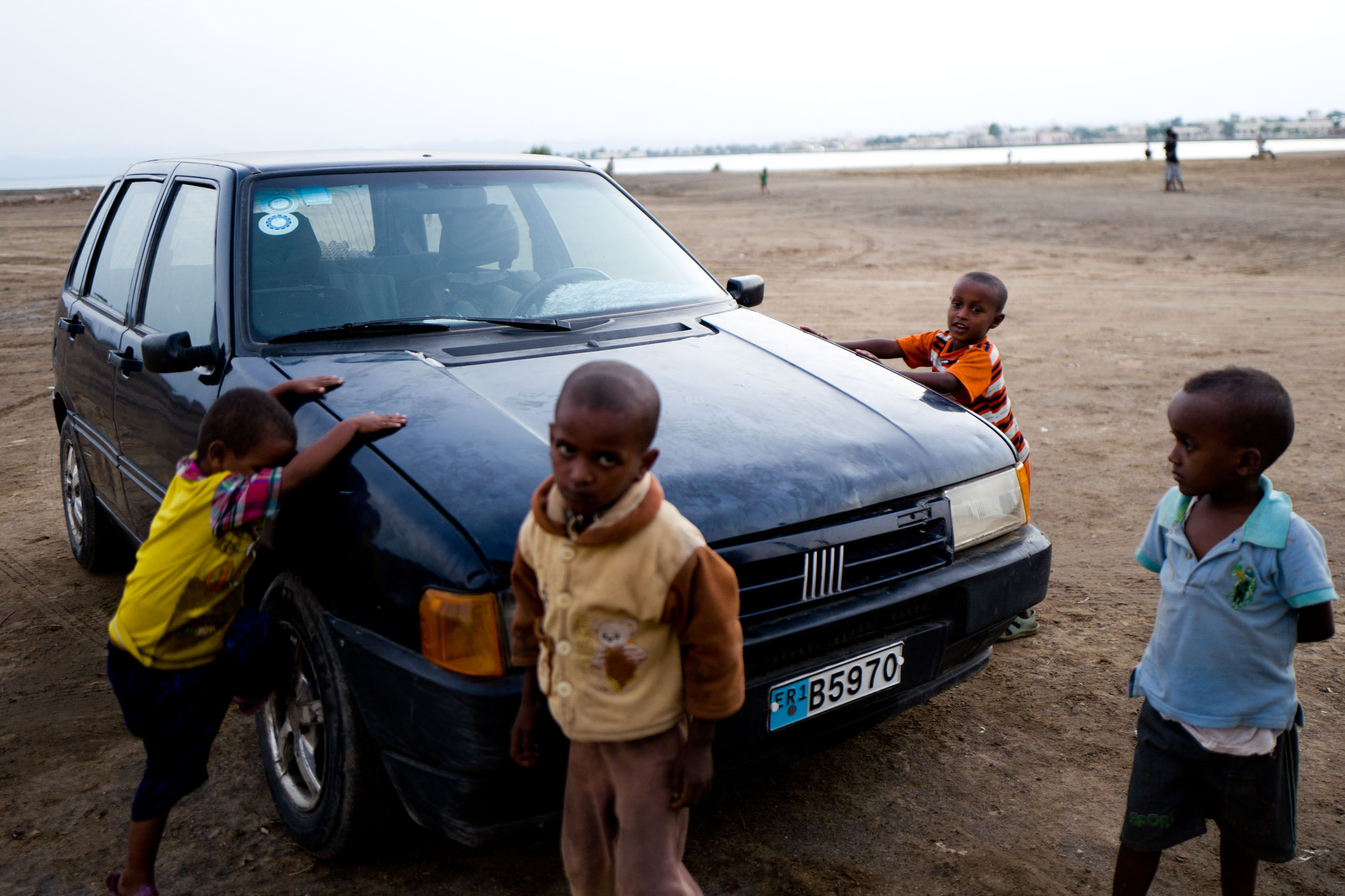 Children playing  next to a Fiat Uno car on the streets of Massawa.