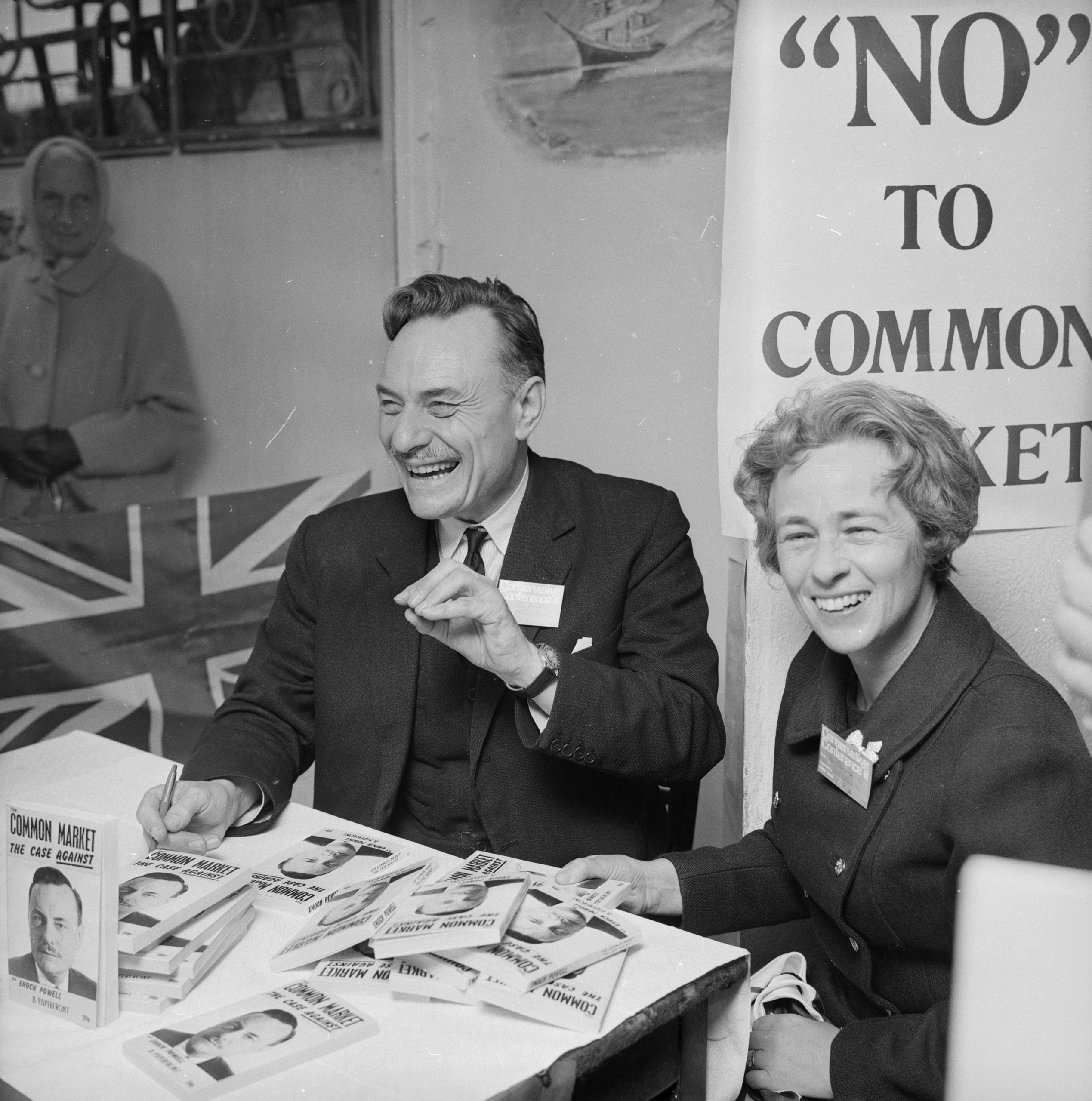 English Conservative politician, (John) Enoch Powell with his wife as he signs copies of his book 'Common Market - The Case Against' during the Conservative Party Conference in Brighton, Oct. 13, 1971