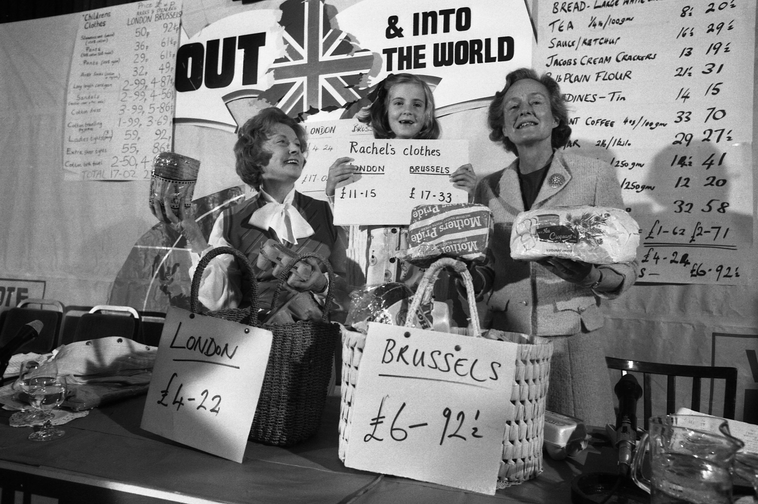 Social Services secretary, Mrs Barbara Castle, left, her 7-year-old great-niece Rachel Hilton and Mrs Joan Marten, wife of Neil Martin, Chairman of the anti-Common Marketeers (unseen) display goods they brought in London and Brussels with their retrospective prices for comparison during a press conference at the Waldorf Hotel in London , May 29, 1975