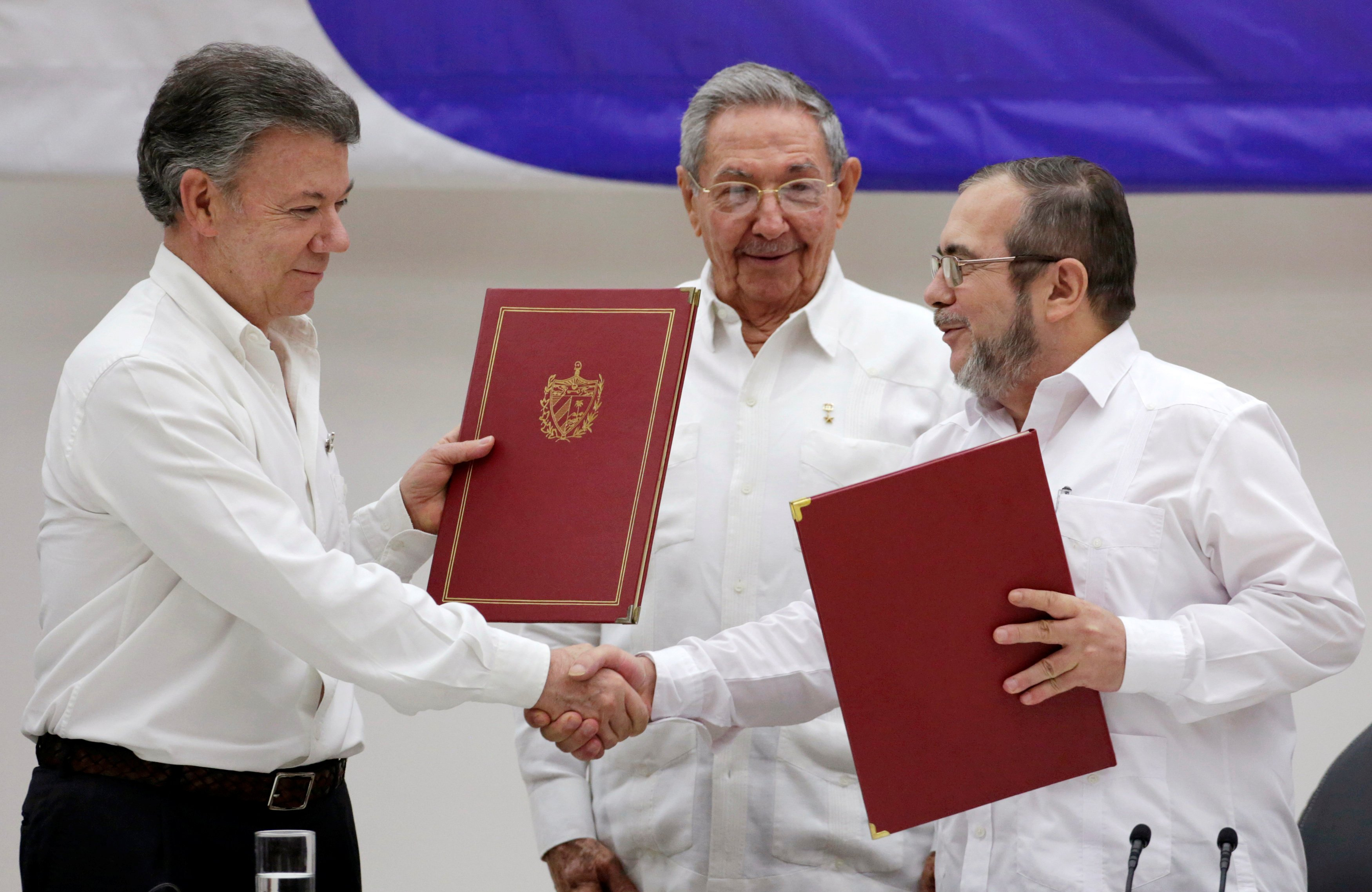 Cuba's President Raul Castro (C), Colombia's President Juan Manuel Santos (L) and FARC rebel leader Rodrigo Londono, react after the signing of a ceasefire deal in Havana, on June 23, 2016.