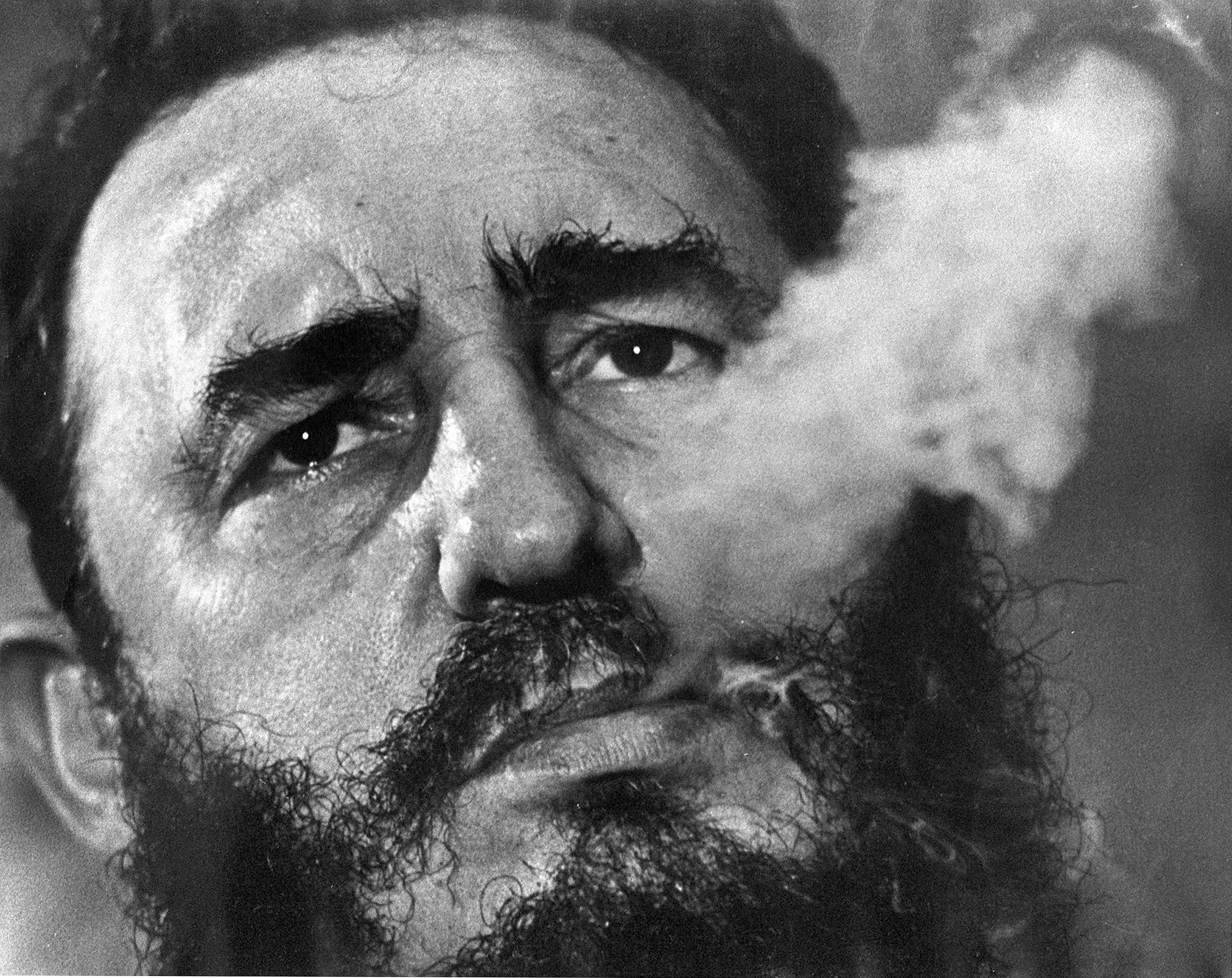 Fidel Castro exhales cigar smoke during an interview at his presidential palace in Havana, March 1985.