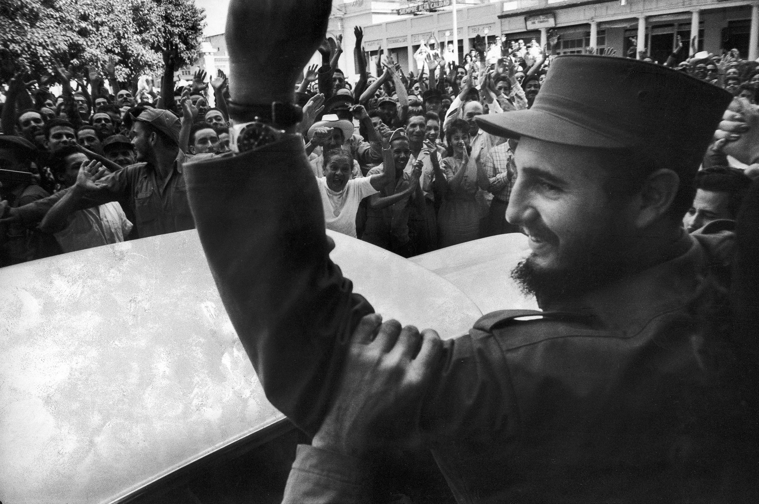 Rebel leader Fidel Castro waves to a cheering crowd on the victorious march to Havana after ousting dictator Fulgencio Batista.