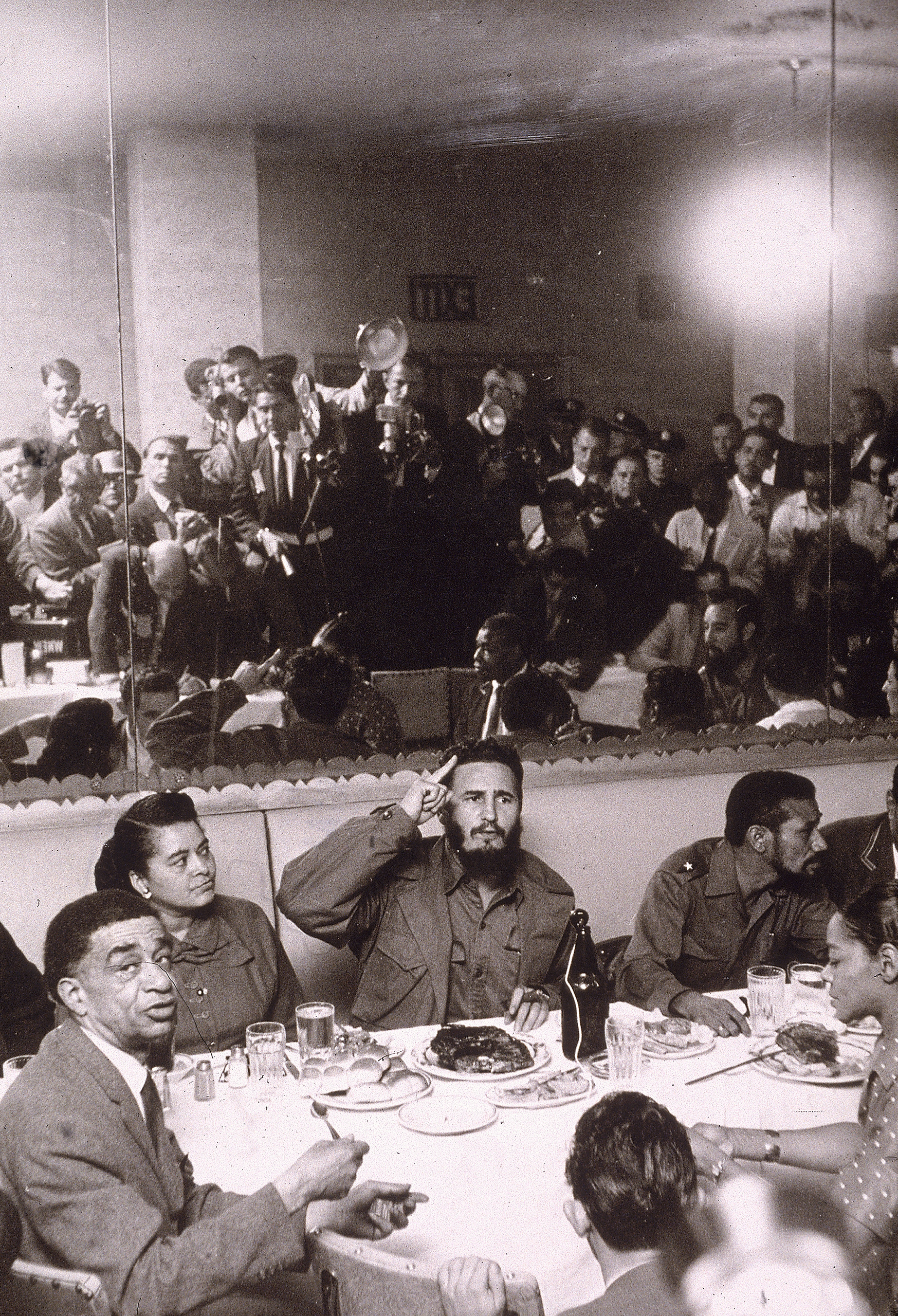 Cuban President Fidel Castro entertains a group of people at a dinner table in Harlem during a trip to New York City, as the press takes photographs in the background, 1959.