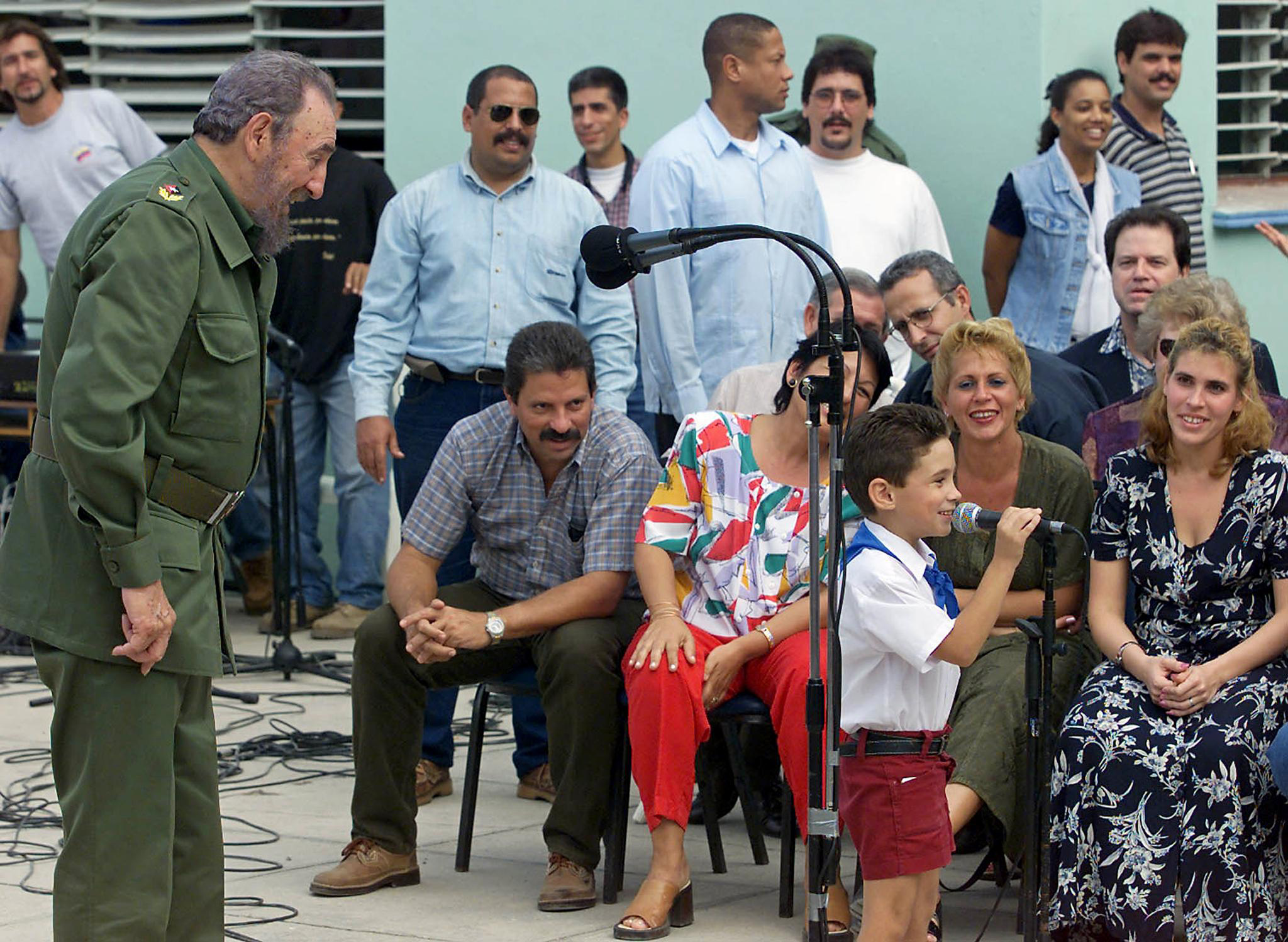 Cuban President Fidel Castro looks at Elian Gonzalez, a former castaway who was returned from the United States, during a party for his seventh birthday at a school in Cardenas, Cuba, on Dec. 6, 2000. Family members and teachers are seated in the background.