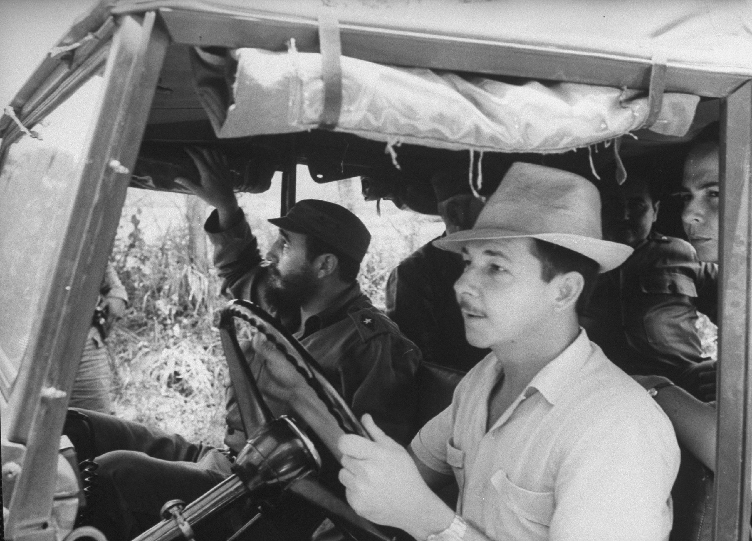 Raul Castro, in white, acts as a chauffeur for his brother, Fidel, in passenger seat, 1964.