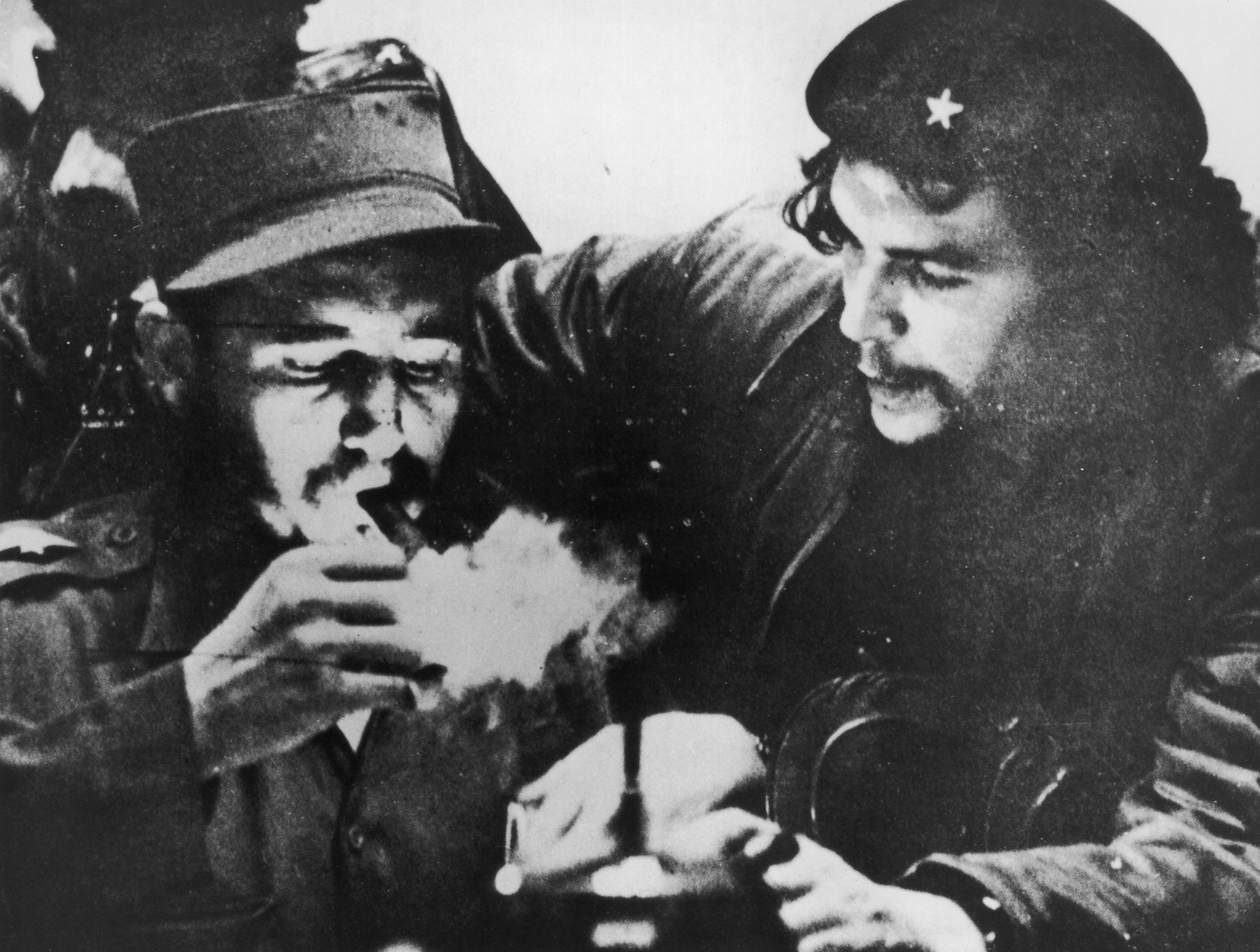 Cuban revolutionary Fidel Castro (left) lights his cigar while Argentine revolutionary Che Guevara looks on in the early days of their guerrilla campaign in the Sierra Maestra Mountains of Cuba, circa 1956. Castro wears a military uniform while Guevara wears fatigues and a beret.