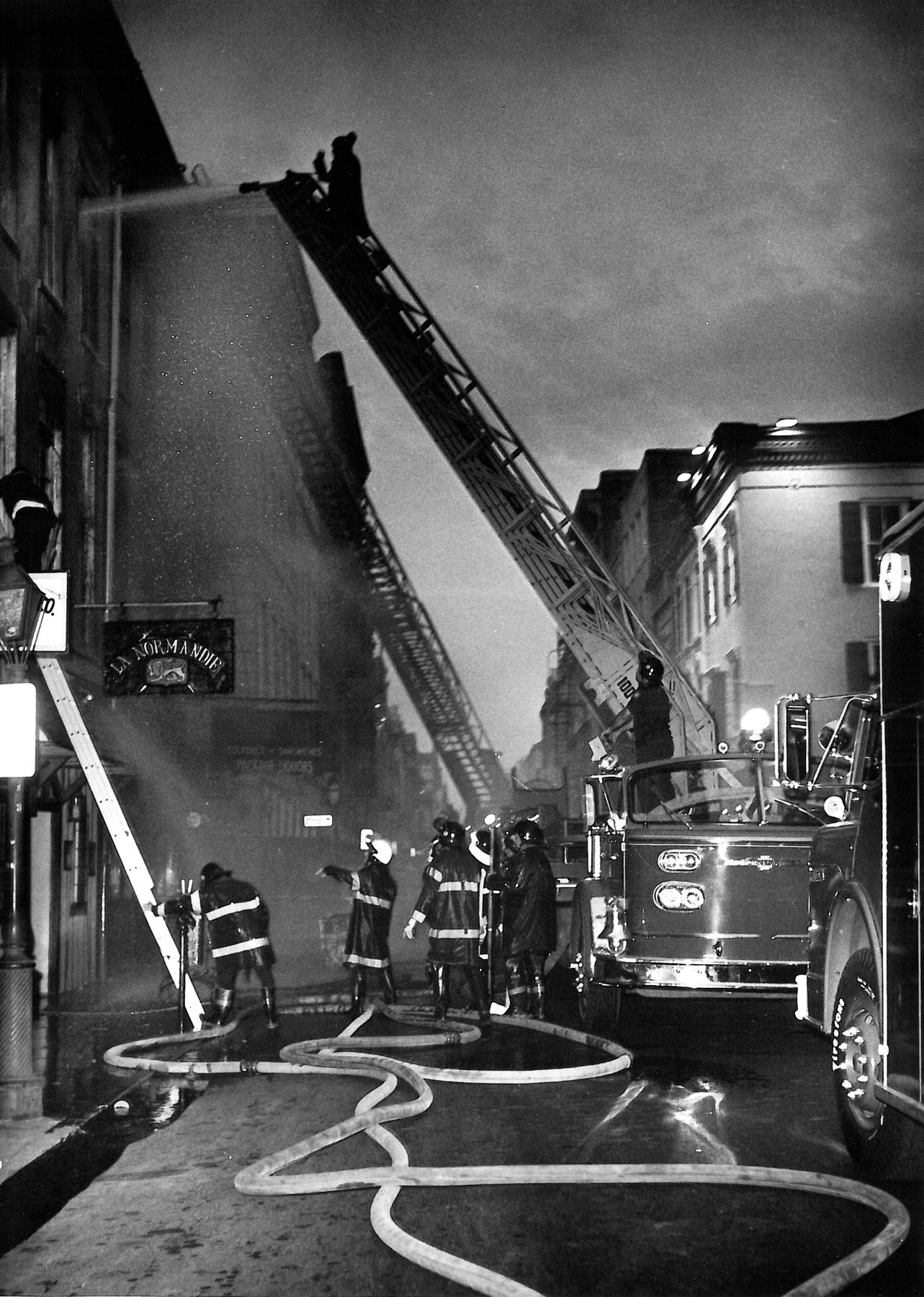 Panic erupted and everyone raced to the windows. They were covered with metal bars. Rasmussen called people to follow him—he knew a back exit. Only about 20 of the 65 patrons heard. Someone on the street called the fire station, but the Upstairs Lounge burned in 16 minutes.