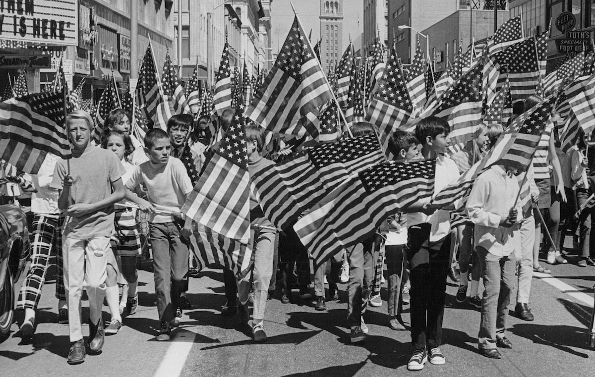 Hundreds of kids with flags, marching along 16th street, in annual flag day parade in downtown Denver in 1970