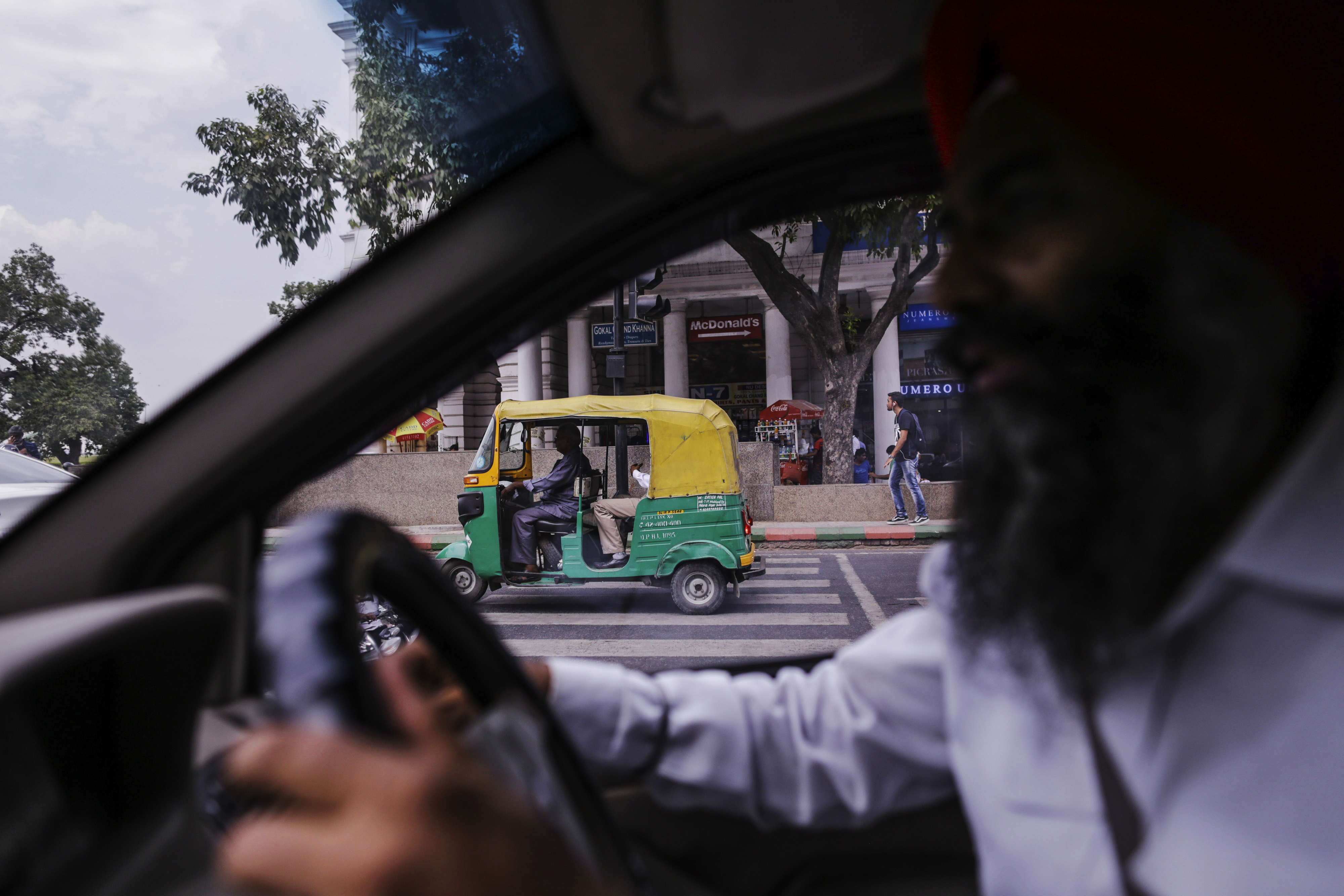 An auto rickshaw travels past Bhag Singh, a driver for the Uber Technologies Inc. ride-hailing service, as he drives a taxi in New Delhi, India, on Friday, Sept. 18, 2015.