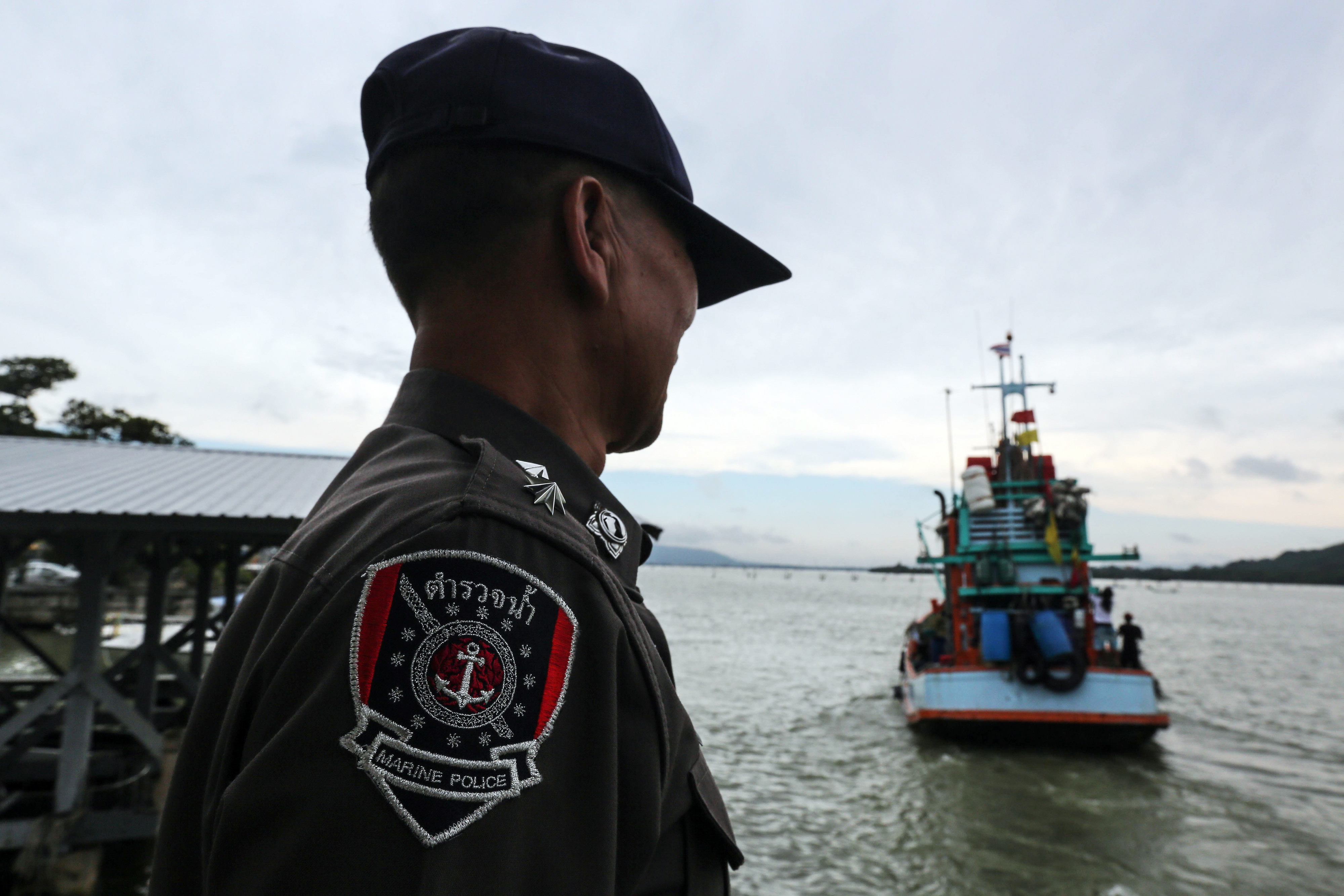 A Royal Thai Maritime Police officer watches a fishing boat leave Songkhla port in Songkhla, Thailand, on Dec. 23, 2015